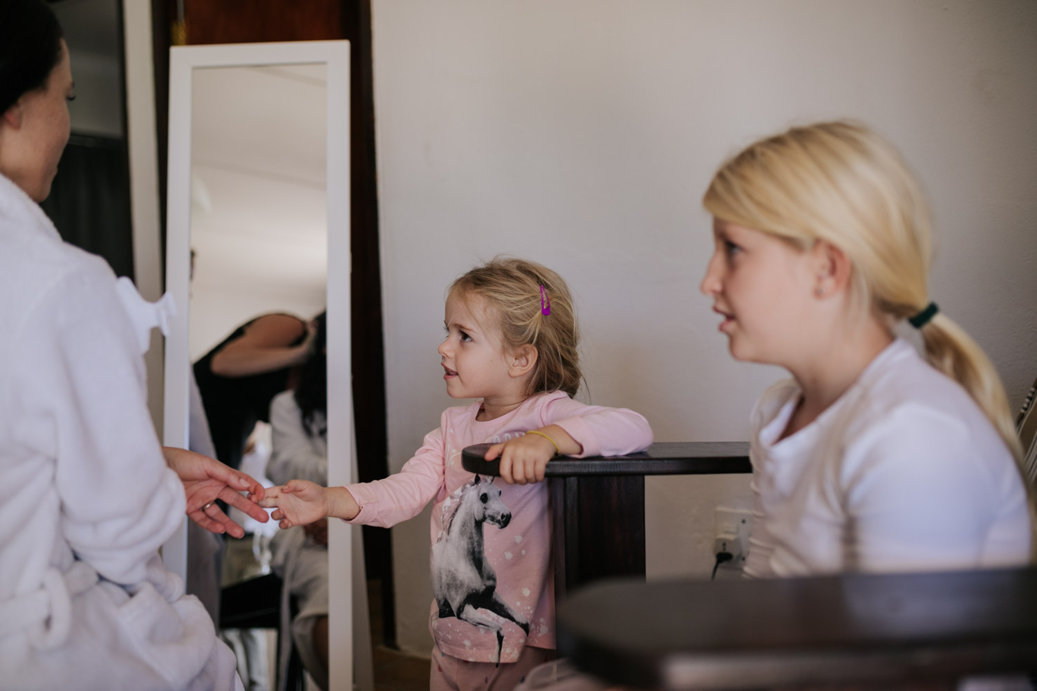 A flower girl holding the bride's hands looking up at her with starry eyes as she gets ready in guest house in Tulbagh, near Riekeek Kasteel