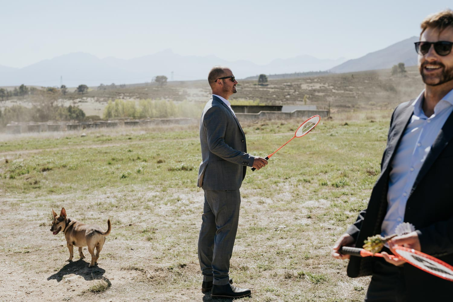 Groom and his best man hanging out with his dog and playing badminton before he gets married on his farm in Tulbagh