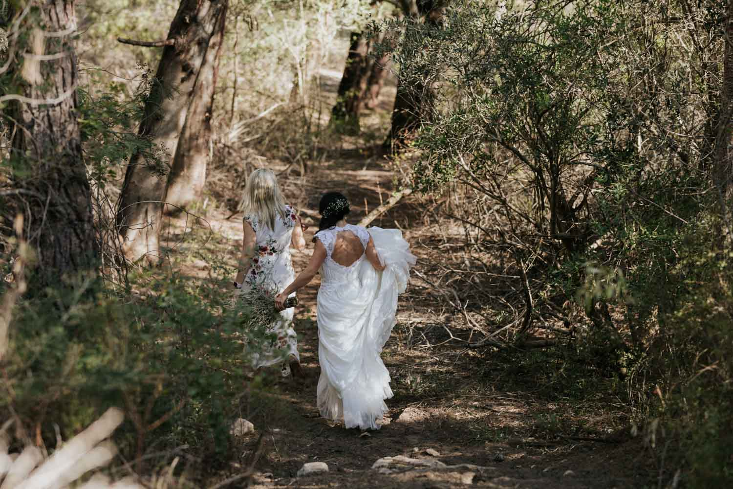 Bride and bridesmaid walking through the forest on the way to get married under the trees, in Tulbagh, Cape Town.