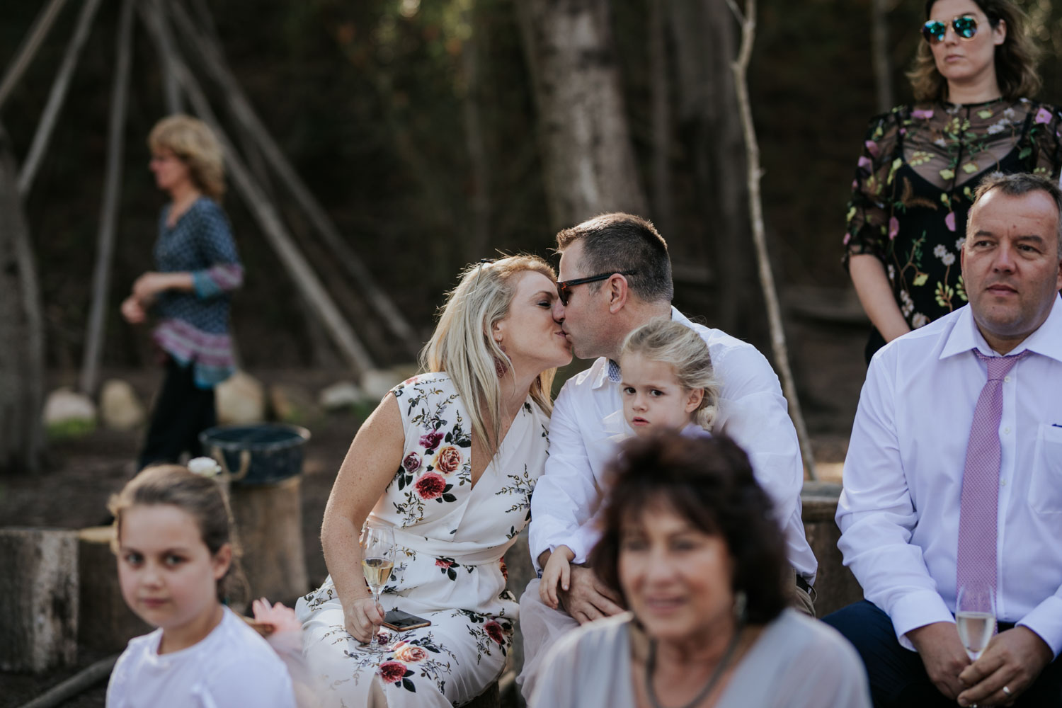 Candid and romantic moment of wedding guests sharing a kiss during a wedding ceremony