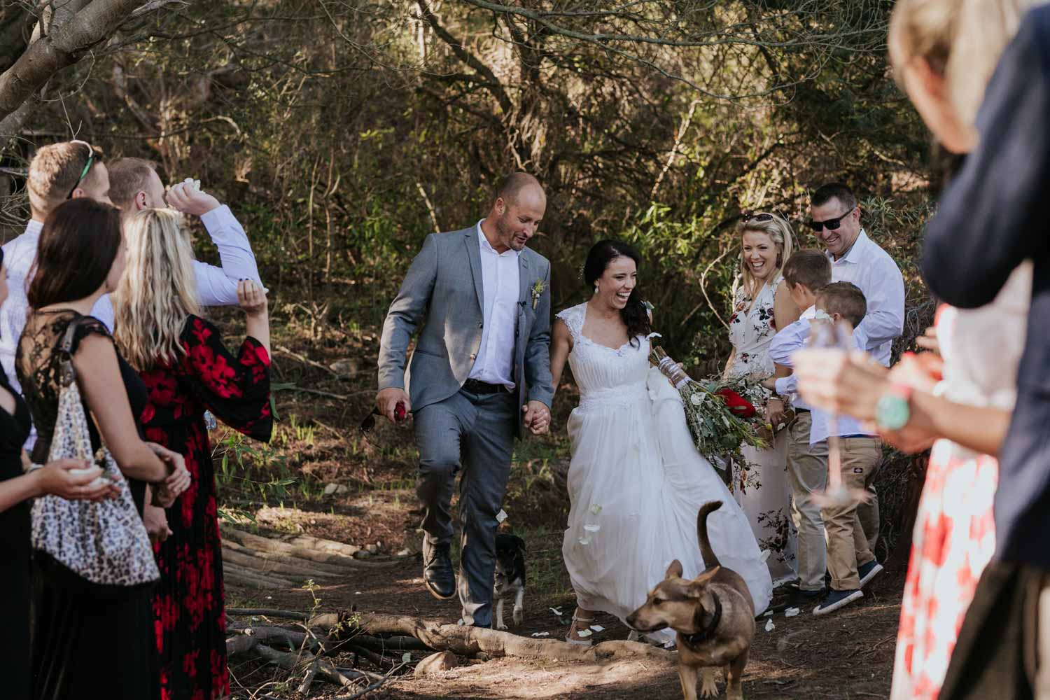 Guests throw rose confetti on husband and wife as they walk down a dusty farm road in Western Cape, South Africa with their dog leading the way.