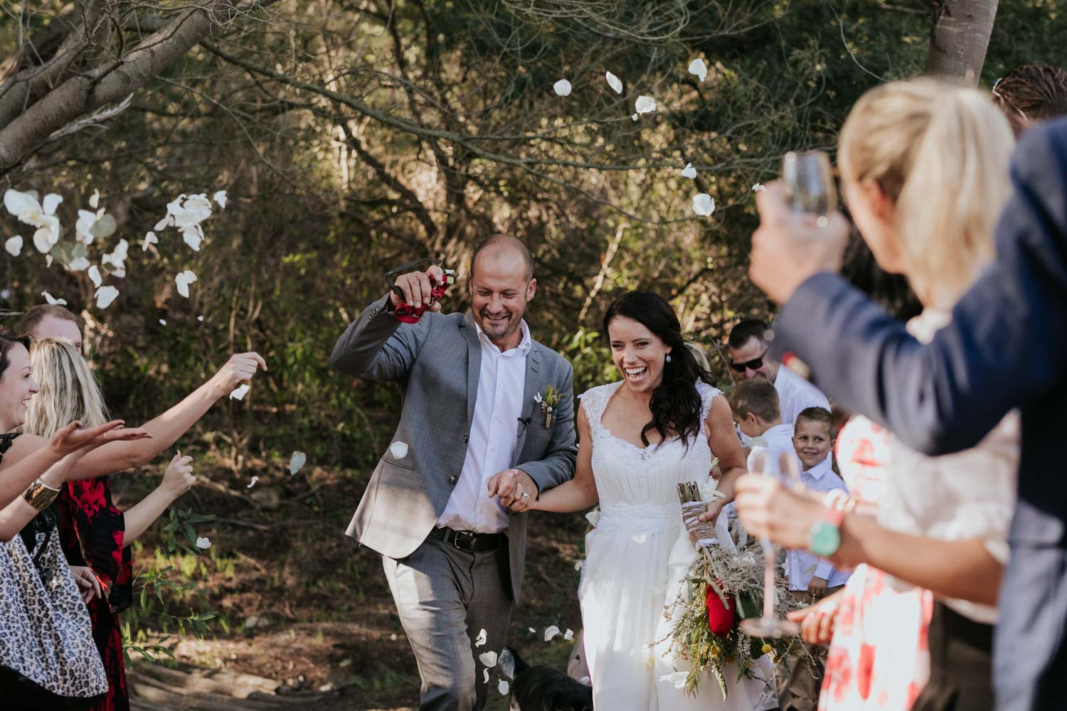 Guests throw rose confetti on husband and wife as they walk down a dusty farm road in Western Cape, South Africa.