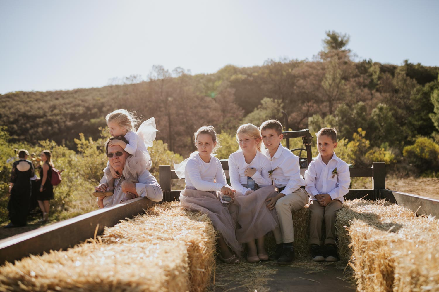 Cute and candid moment of flower girls and page boys sitting in hay bails in the back of an old farm tractor