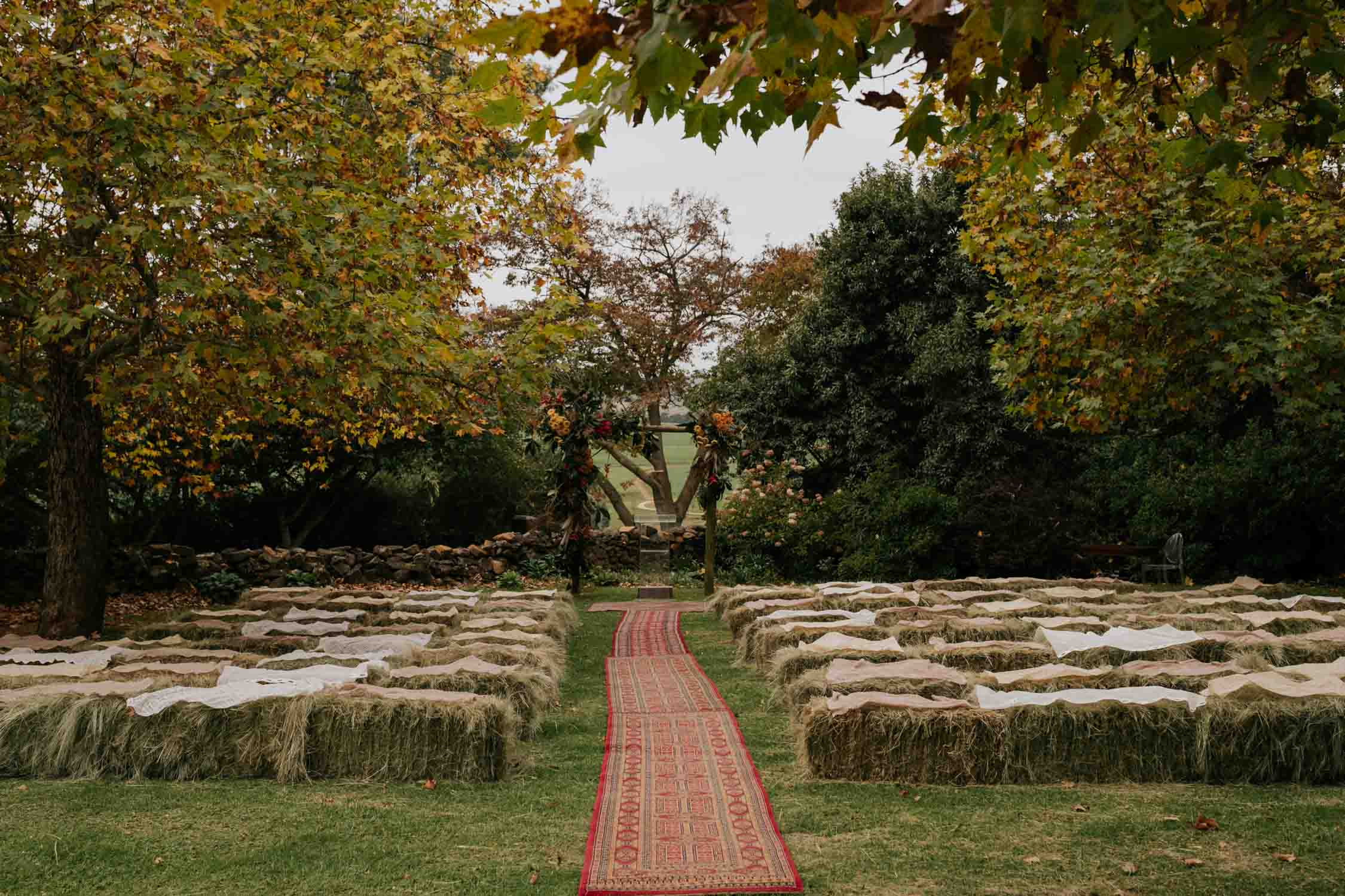 Wedding aisle with red Persian carpet under trees on lawn with hay bales as the chairs on a farm