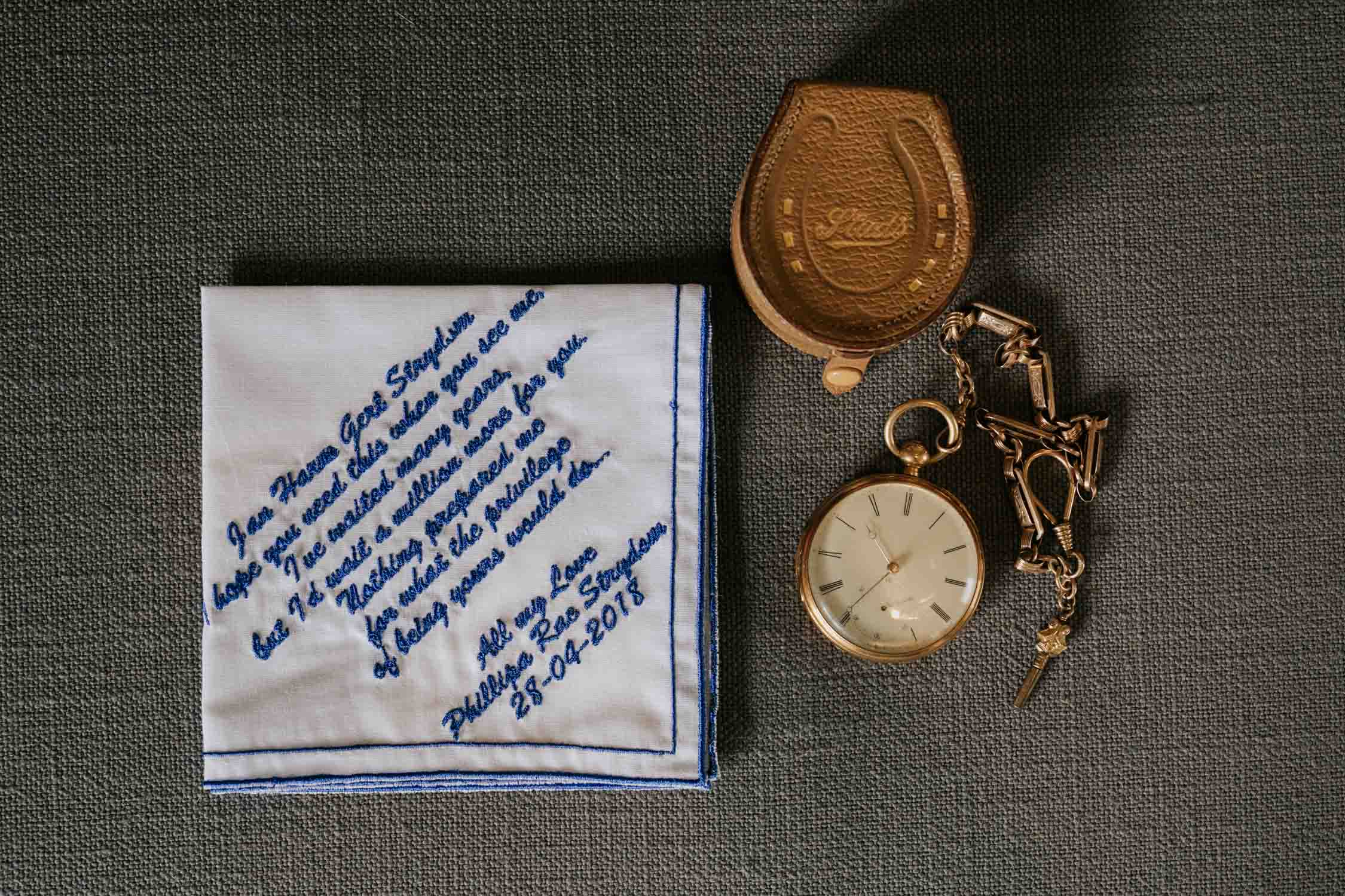 Groom's accessories in a flat lay. Personalised embroidered handkerchief with studs leather box for cufflinks and old vintage pocket watch
