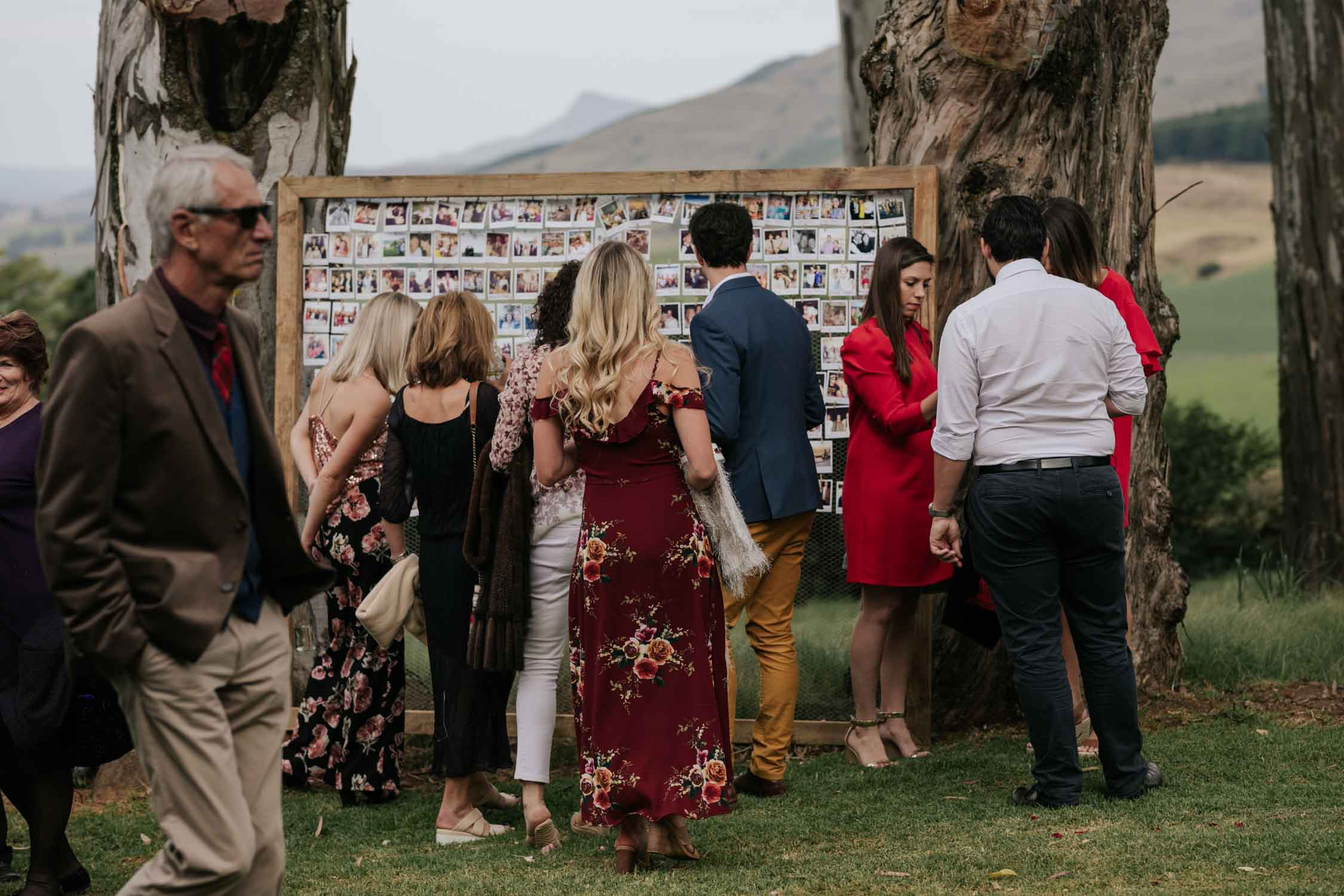 Guests looking at the seating chart at a wedding. The seating chart is made up of photographs of each guest pegged onto a wood and wire frame.