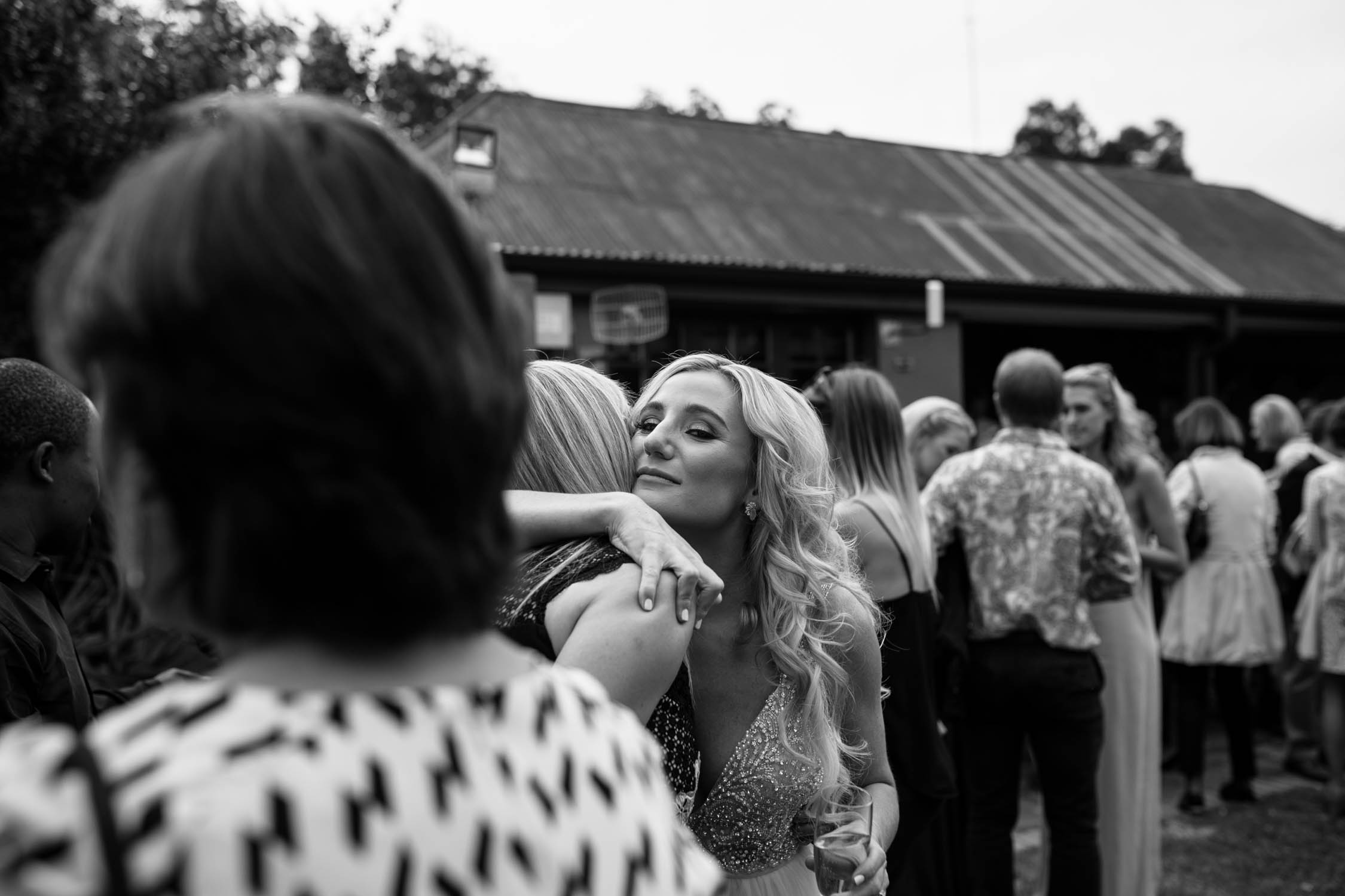 Bride hugging a friend after wedding ceremony. Friend is congratulating her on her marriage.