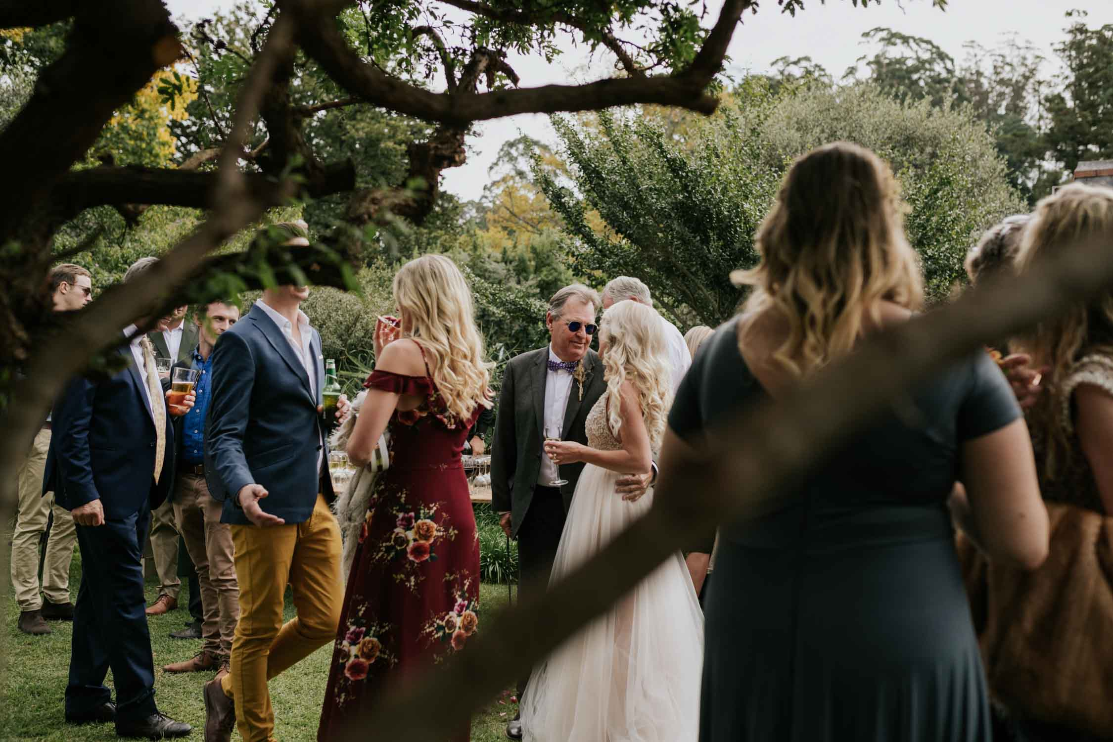 Guests socialising at farm wedding under the trees.