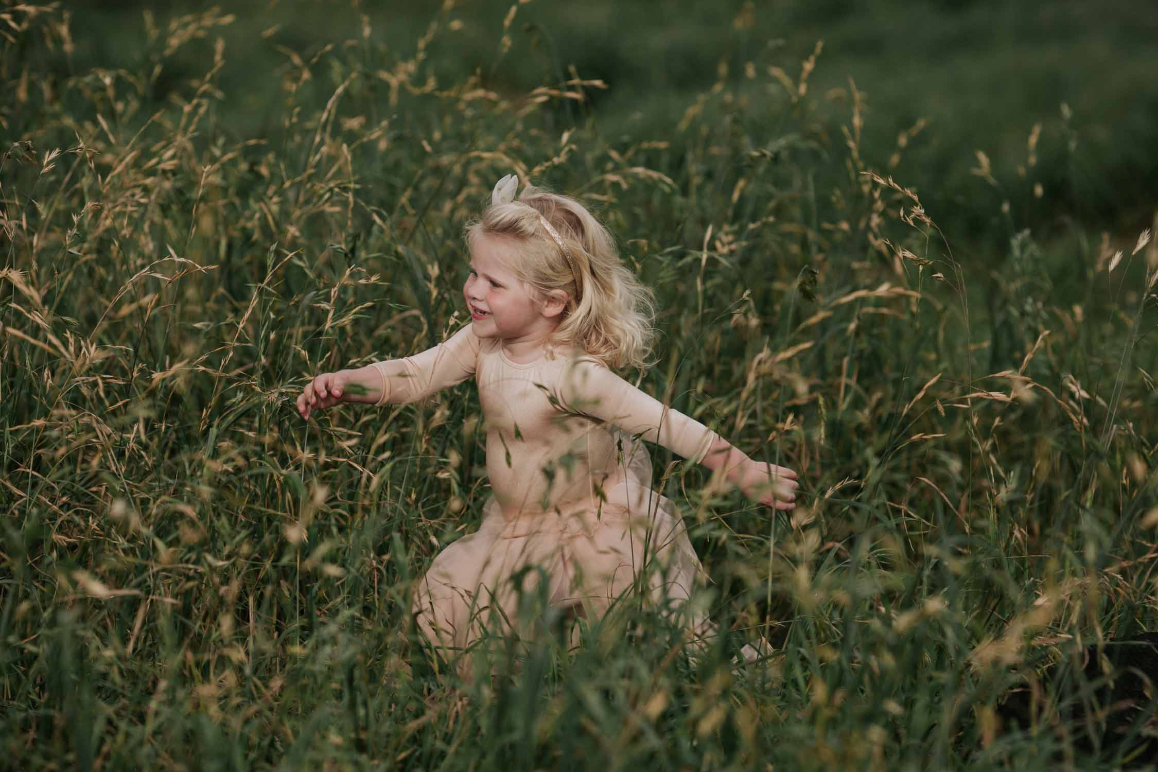 Flower girl running through the field wearing a cute pink outfit.