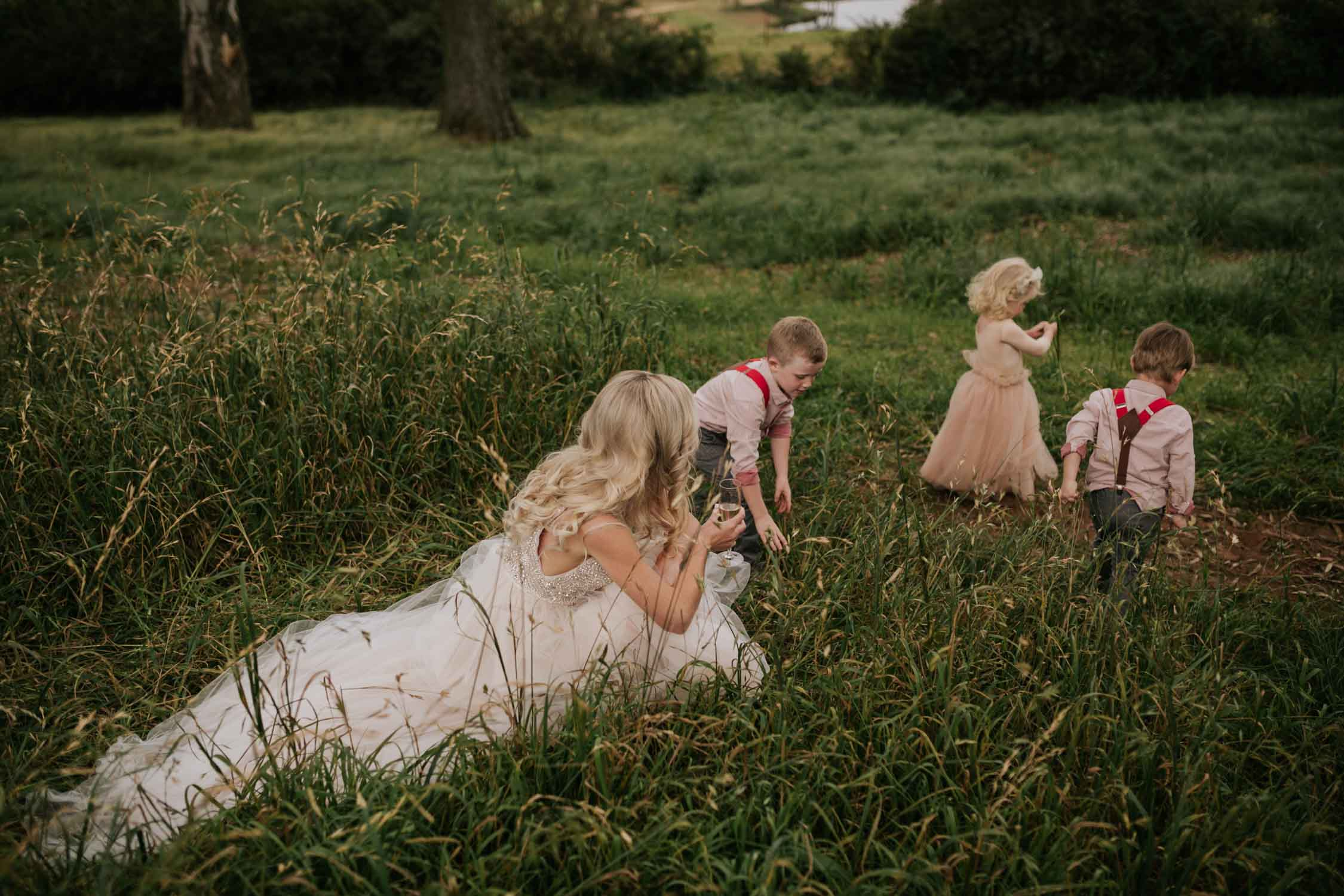 Candid and natural moment of bride with flower girl and page boys in a field