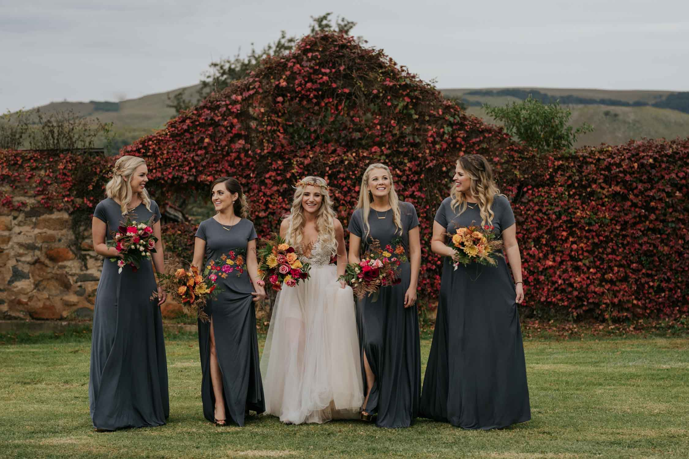Bride who looks like game of thrones mother of dragons with her bridesmaids walking and laughing together at her farm wedding in front of a old ruin building. Candid and natural retinue photographs.