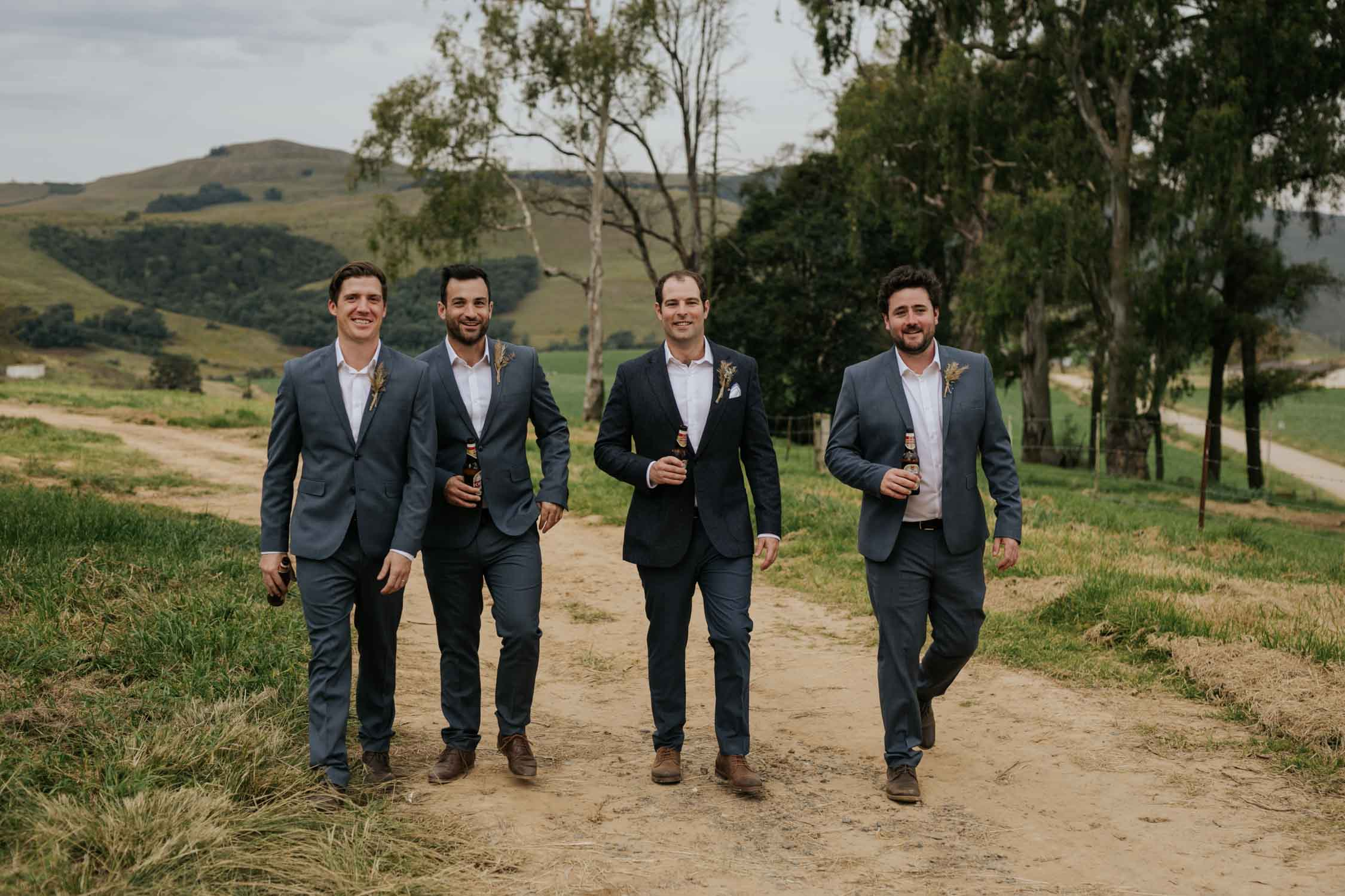 Groom and groomsman wearing grey suits walking on a farm road drinking a beer together. Candid and natural retinue photographs.