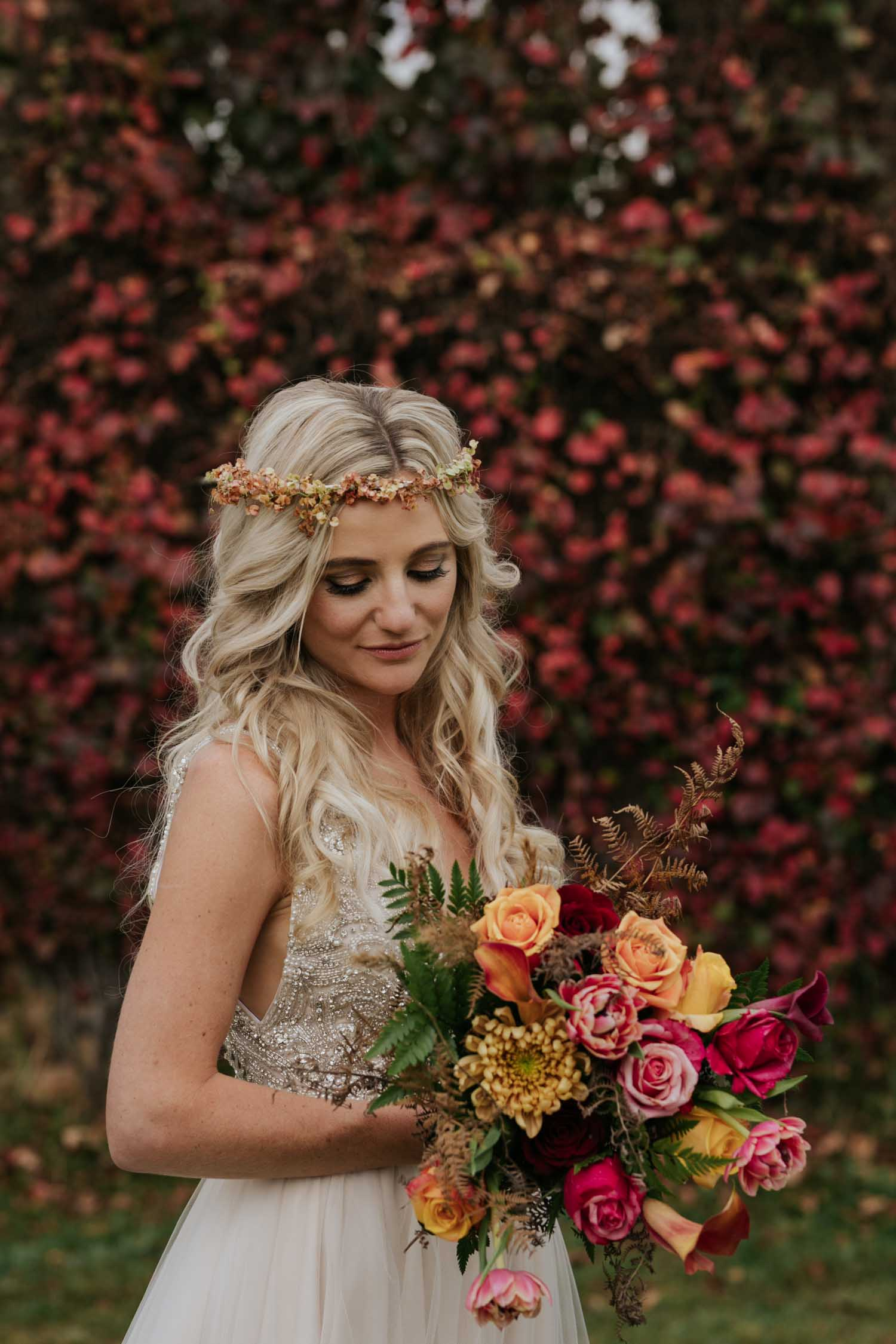 Bride wearing dried flower flower crown and wearing a beaded dress with a jewelled coloured bouquet made up of pink, and burnt orange flowers with dried leaves in it. She looks like Daenerys Targaryen from Game of Thrones.
