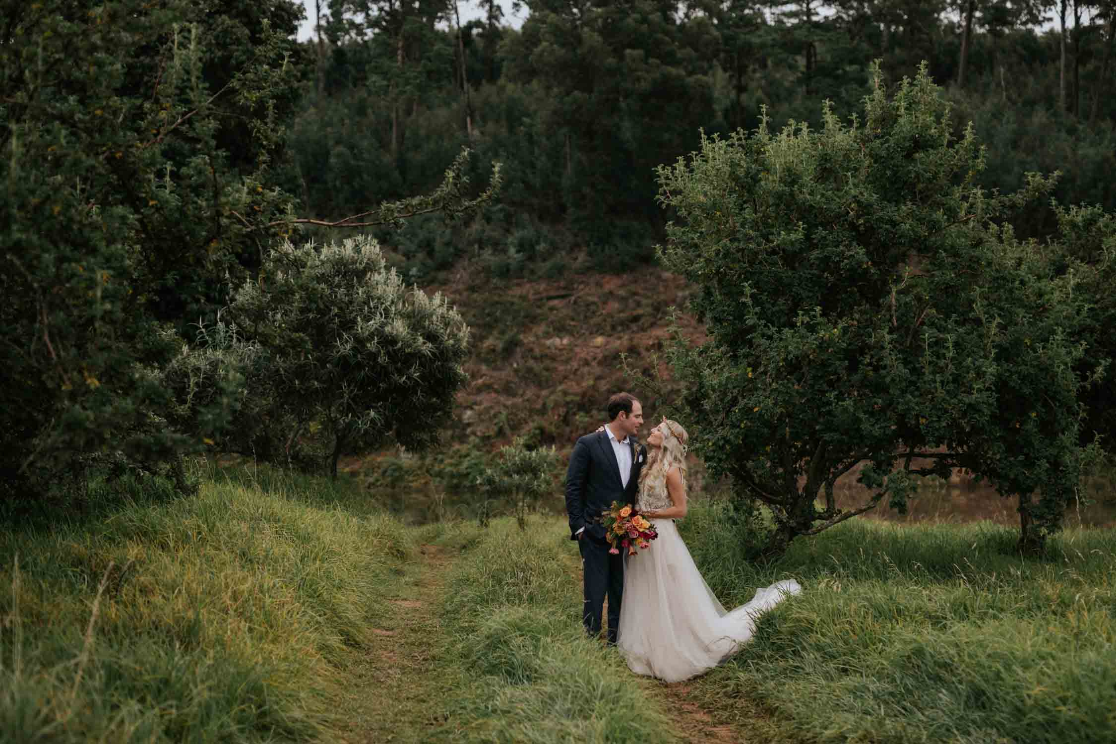 Bride and groom standing on a field at their farm wedding in the Natal Midlands in South Africa.