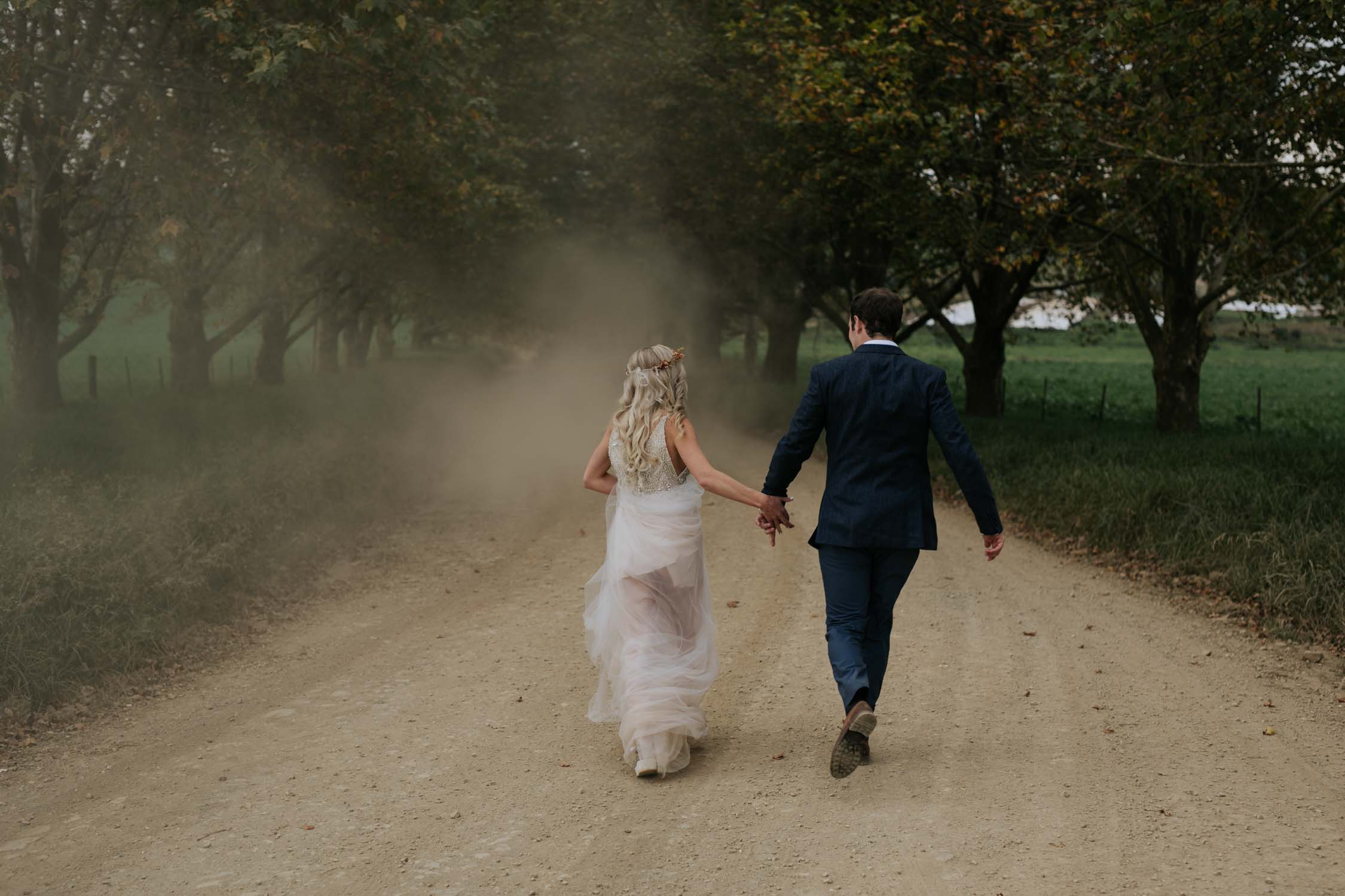 Bride and groom walking down farm road and laughing together under Autumn trees in the Natal Midlands. Candid and natural wedding photographers in South Africa and Vancouver.