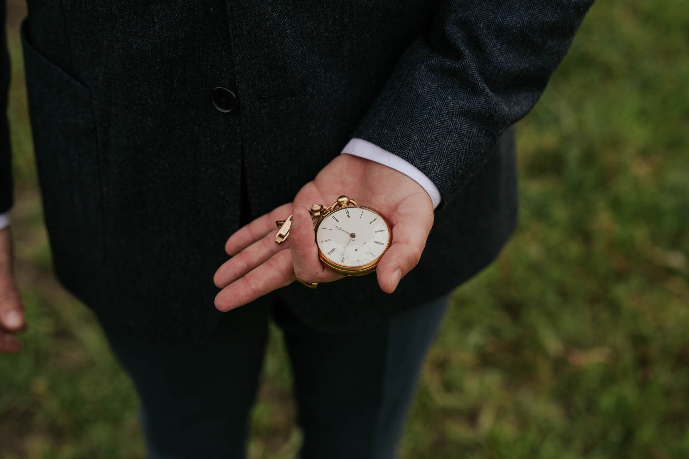 Groom looking at watch before his bride walks down the aisle. He is holding an old pocket watch. His grandfather's - a family heirloom.