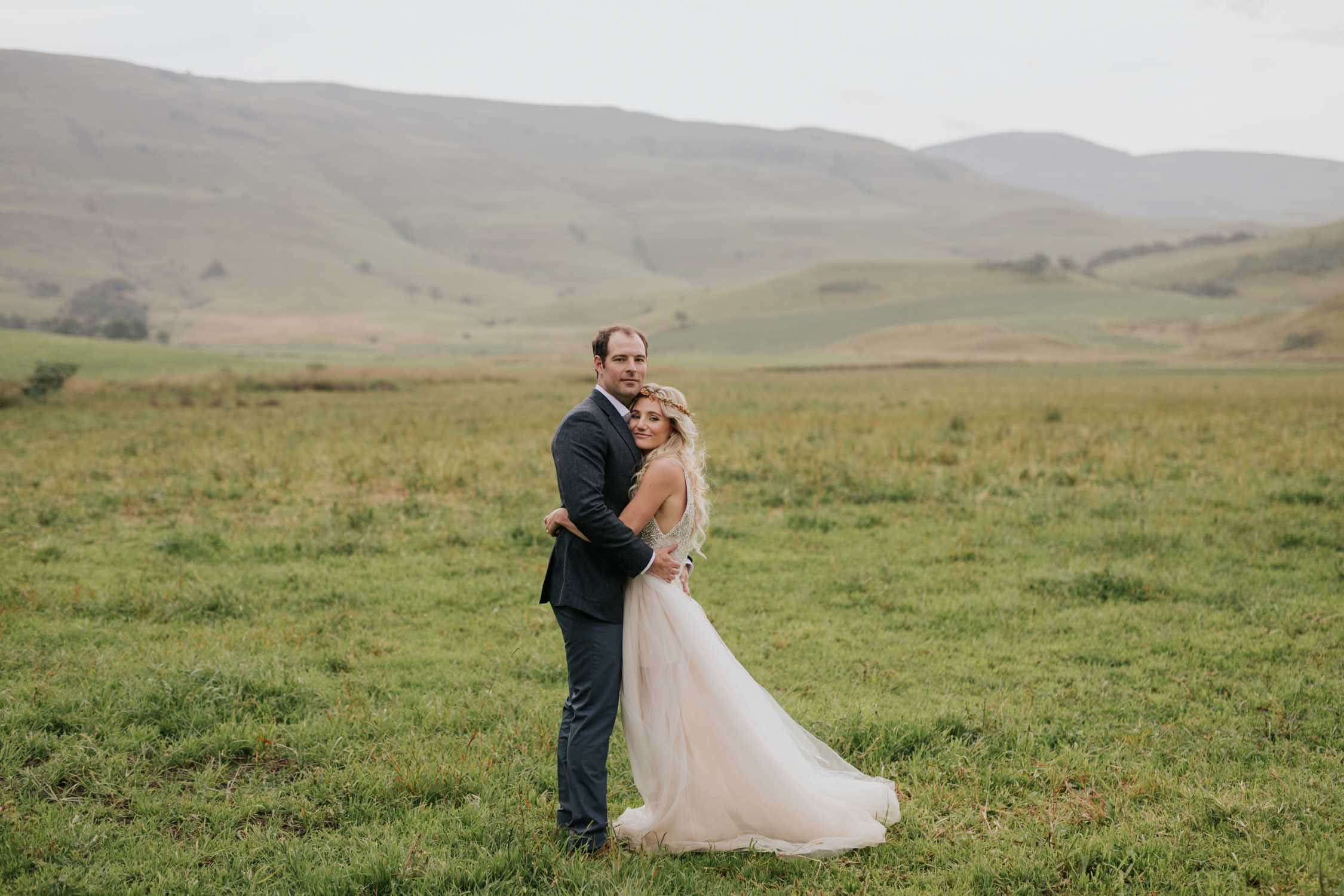 Bride and groom surrounded by green hills and fields at a farm wedding venue in the Natal Midlands.