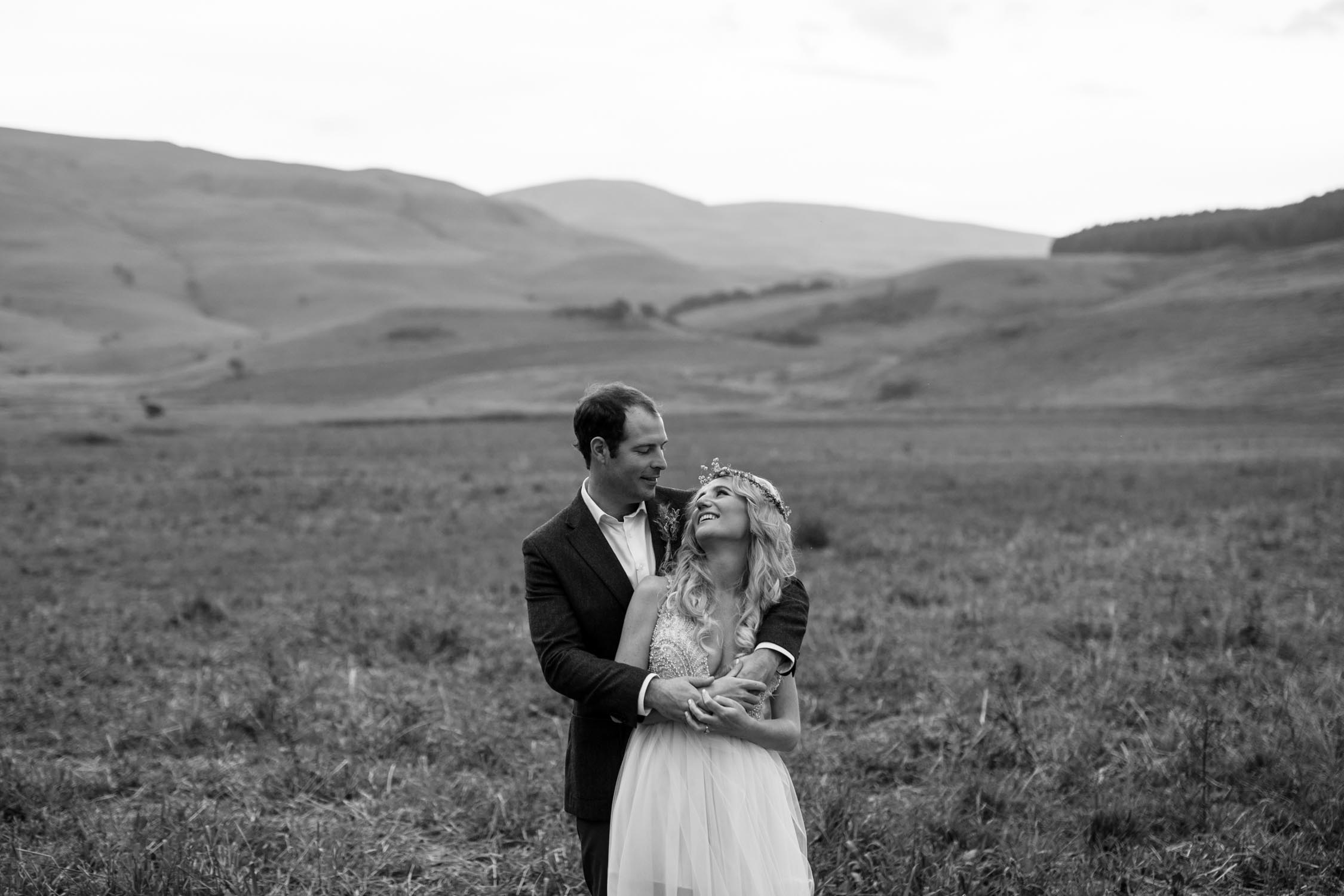 Candid moment of bride and groom looking at each other. Bride and groom surrounded by green hills and fields at a farm wedding venue in the Natal Midlands.