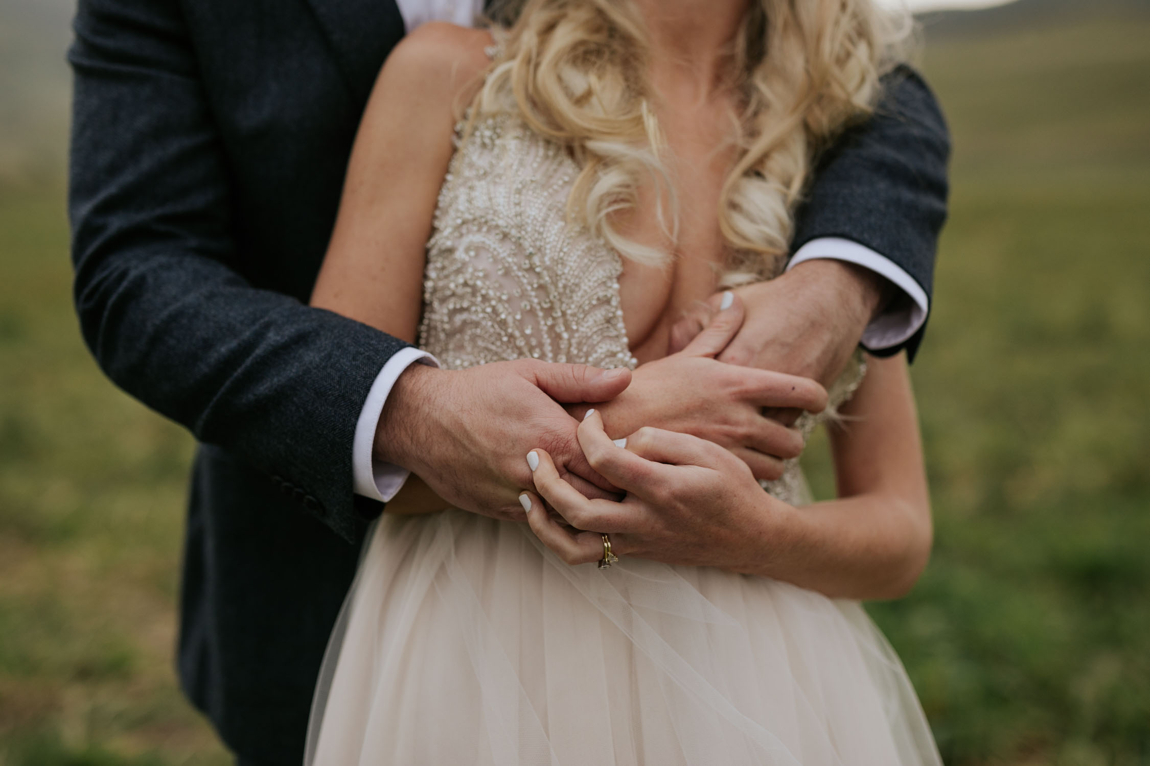 Close up photograph of bride and grooms hands at wedding. They are holding on to each other. Romantic and candid moment.