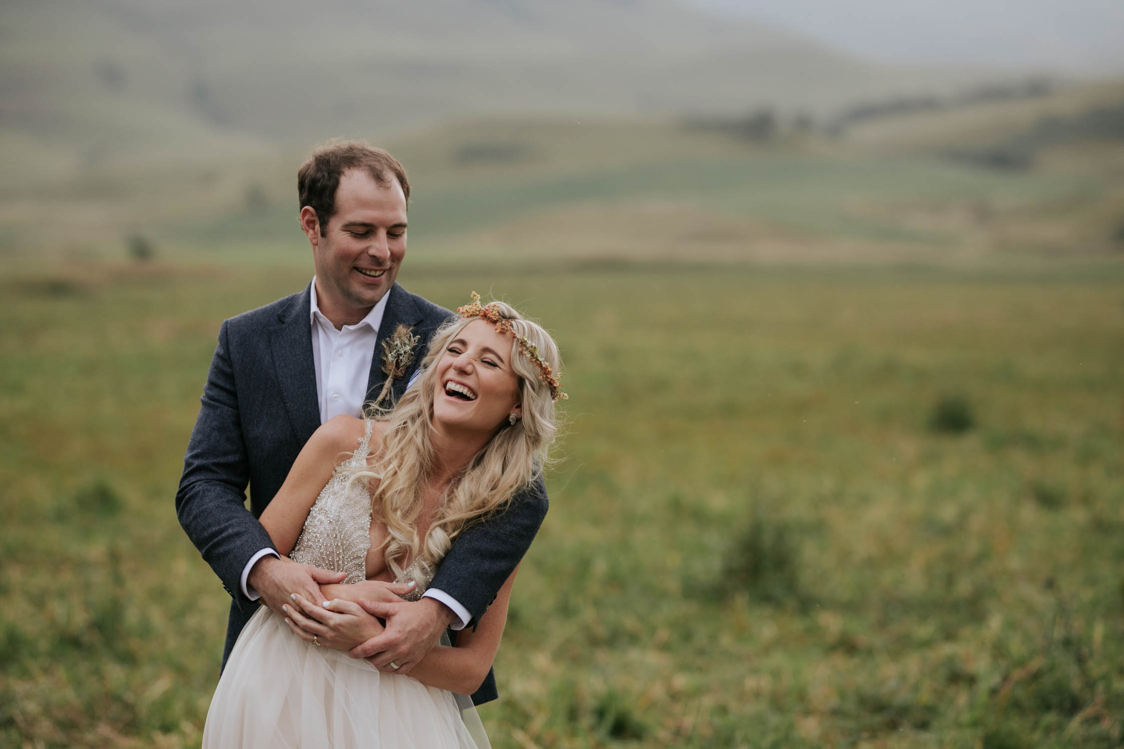 Candid moment of bride and groom looking at each other and laughing and having a lot of fun. Bride and groom surrounded by green hills and fields at a farm wedding venue in the Natal Midlands.