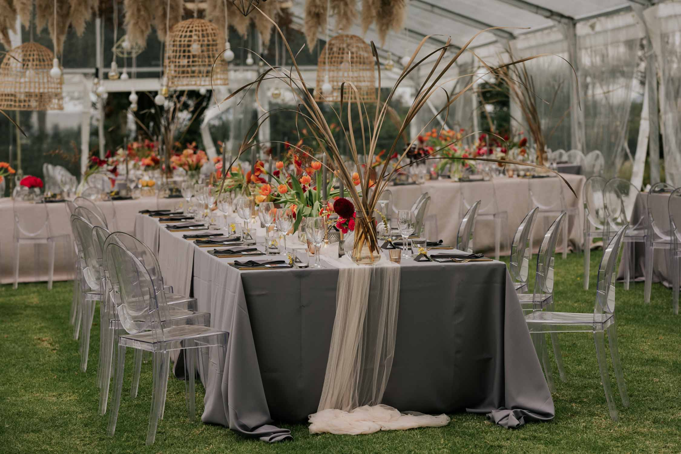 Wedding tables set in glass tent with velvet table cloths with bright flowers and dried flowers