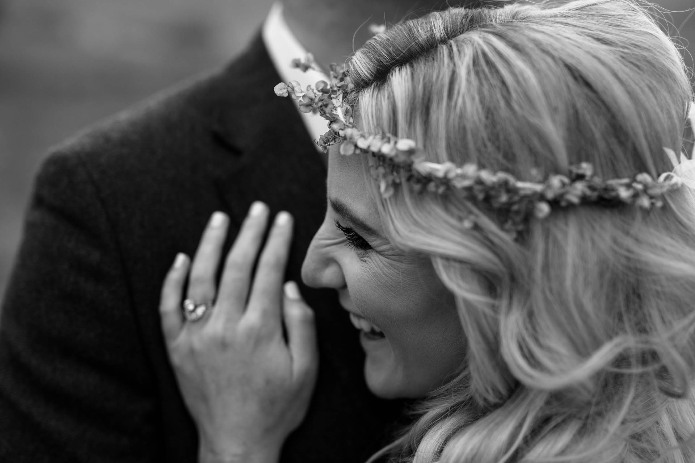 Candid close up moment of bride laughing wearing a flower crown made from dried flowers. Bride and groom surrounded by green hills and fields at a farm wedding venue in the Natal Midlands.