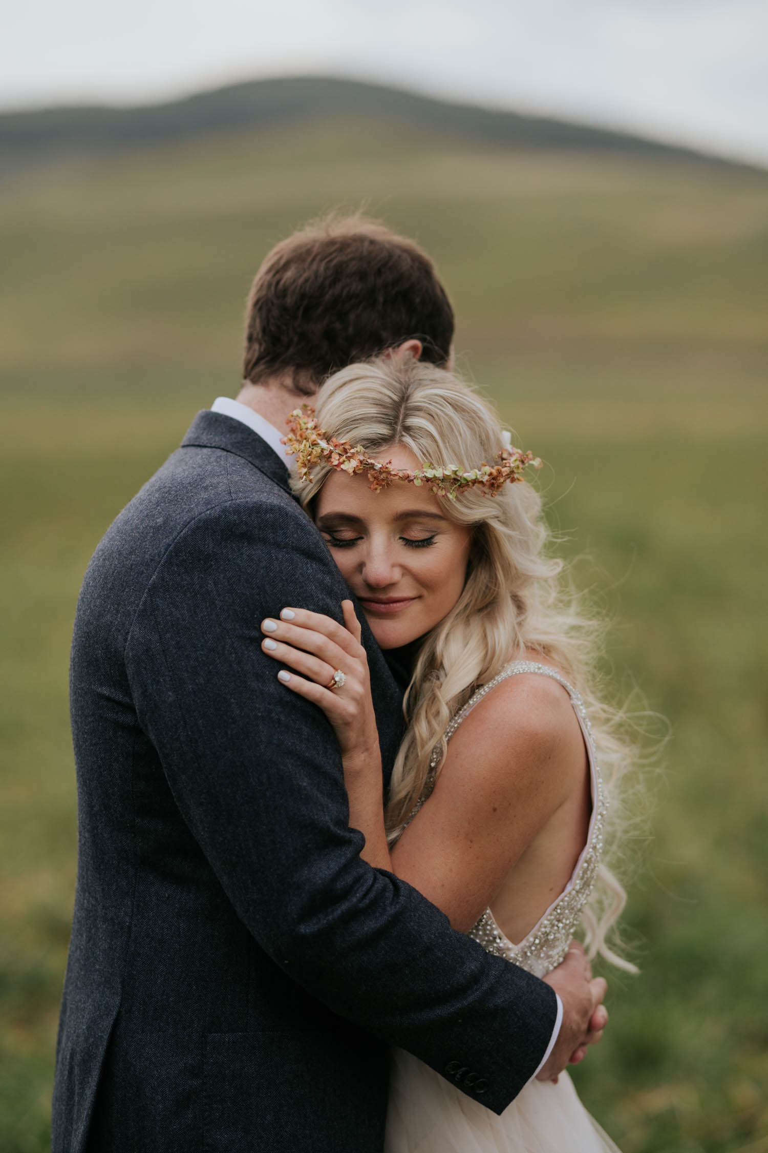 Candid moment of bride holding onto her groom. She is wearing a flower crown made up of dried flowers. Bride and groom surrounded by green hills and fields at a farm wedding venue in the Natal Midlands.