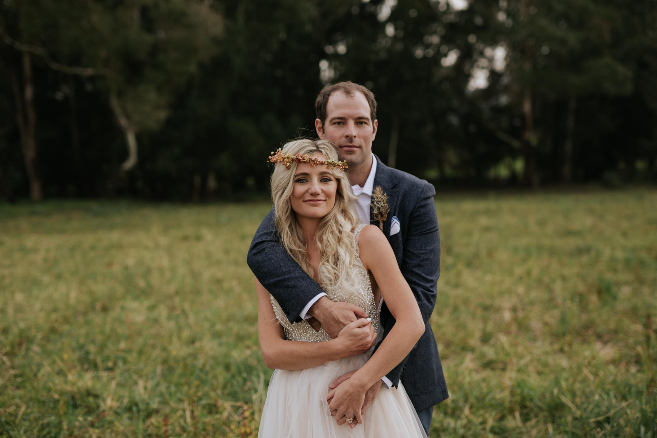 Bride and groom looking at the camera. He is holding her and they are standing in a field on their wedding day in the Natal Midlands near Notthingham Road.