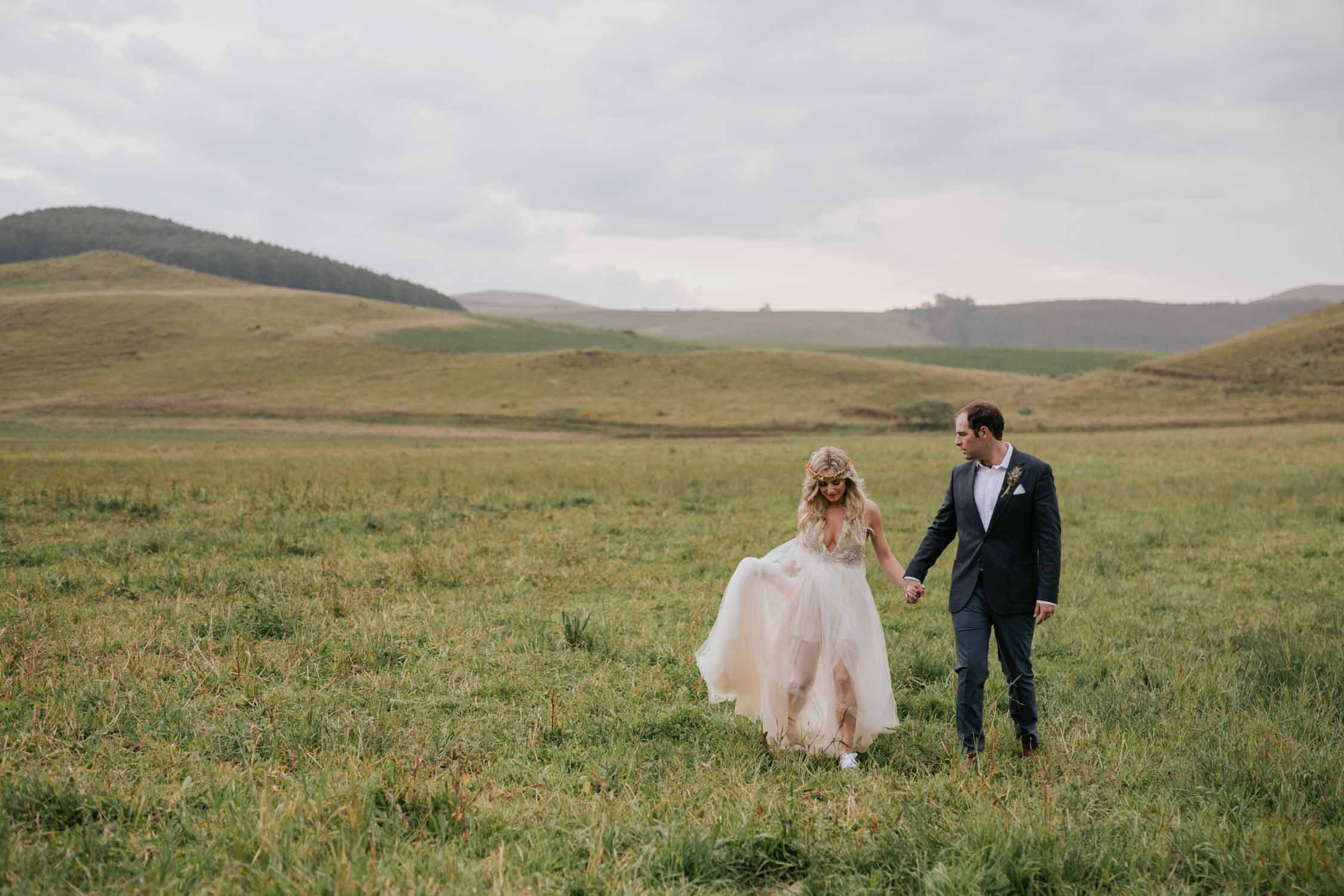 Bride and groom surrounded by green hills and fields at a farm wedding venue in the Natal Midlands near Nottingham Road. Bride is wearing shorts under her wedding dress.