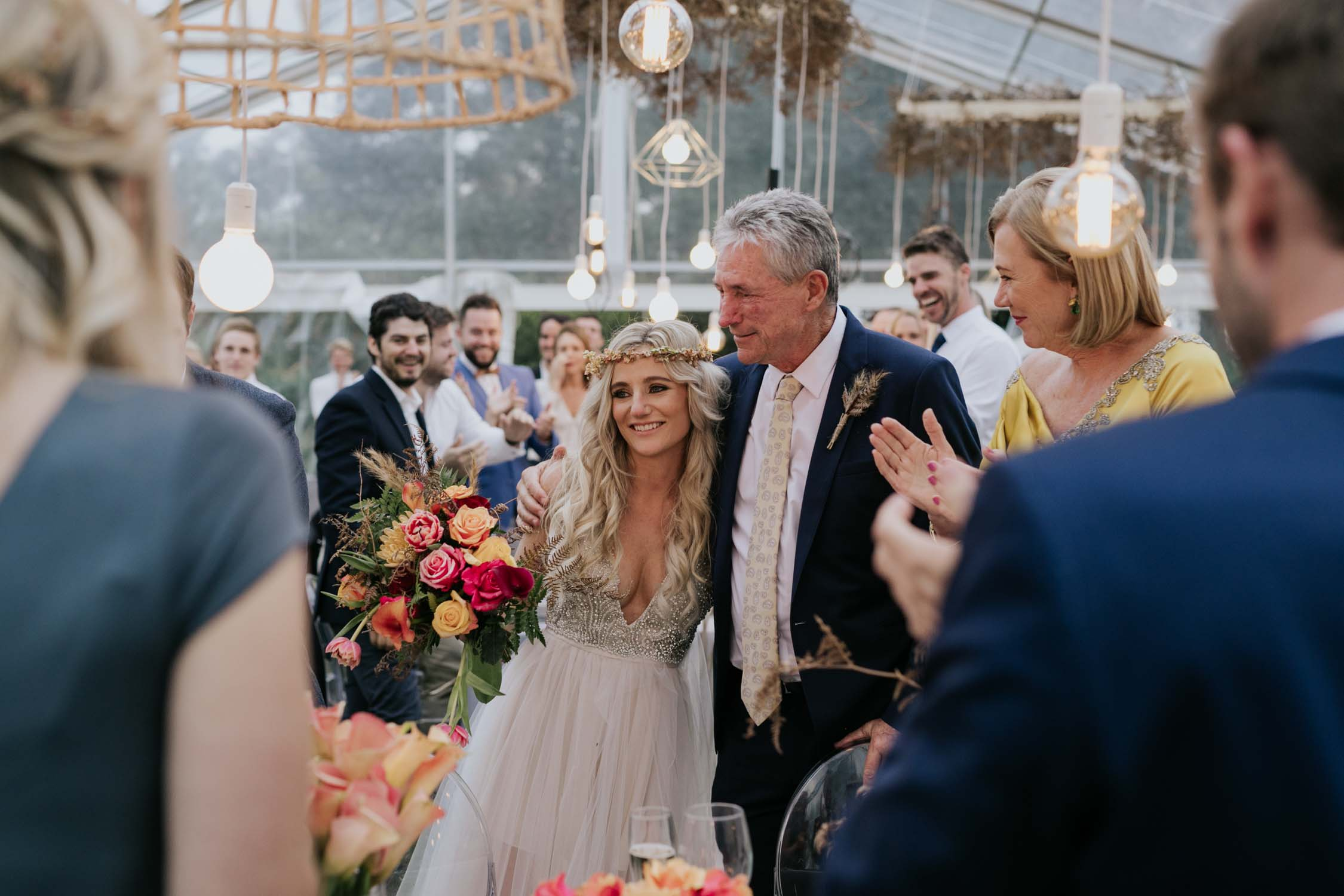 Father of the bride embracing his daughter during the wedding reception. Documentary photographic moment candid and natural.