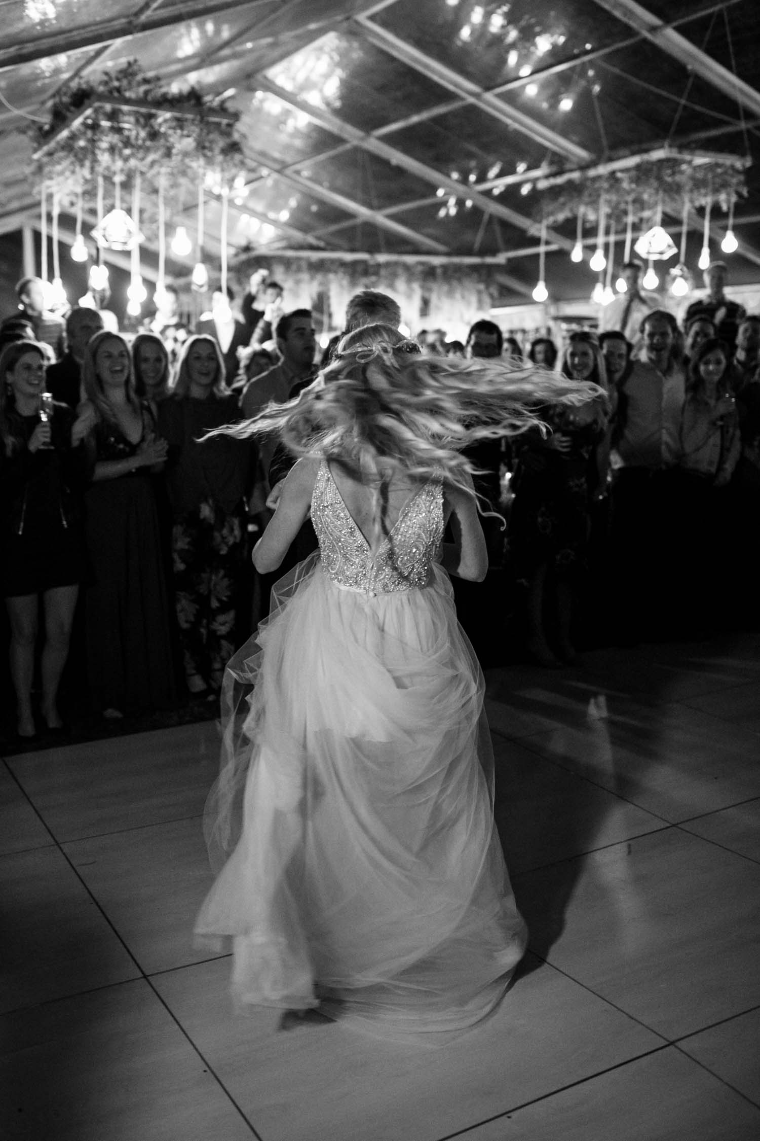 Bride and groom's first dance surrounded by their family and friends