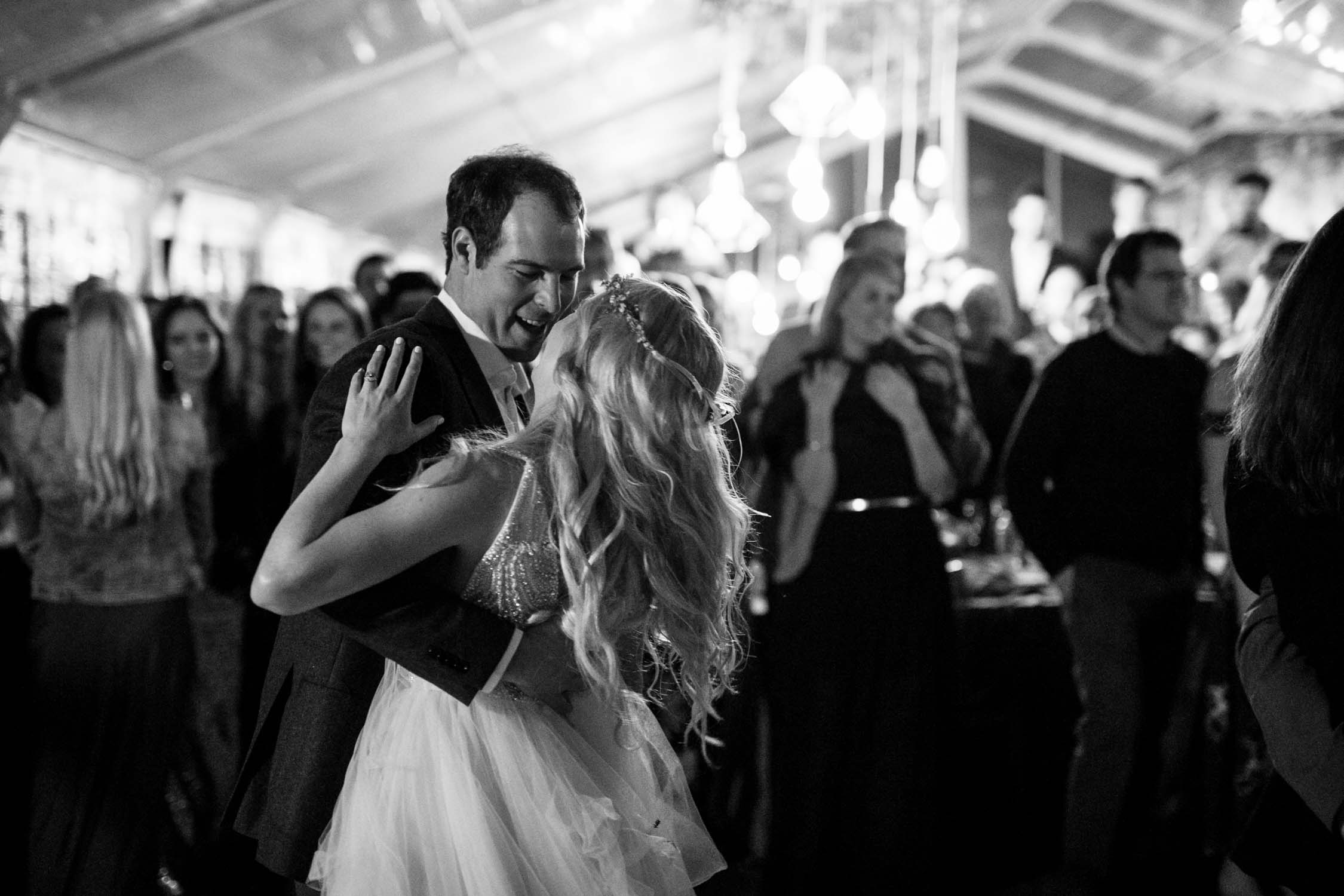 Bride and groom's first dance surrounded by their family and friends. They are having so much fun dancing together.