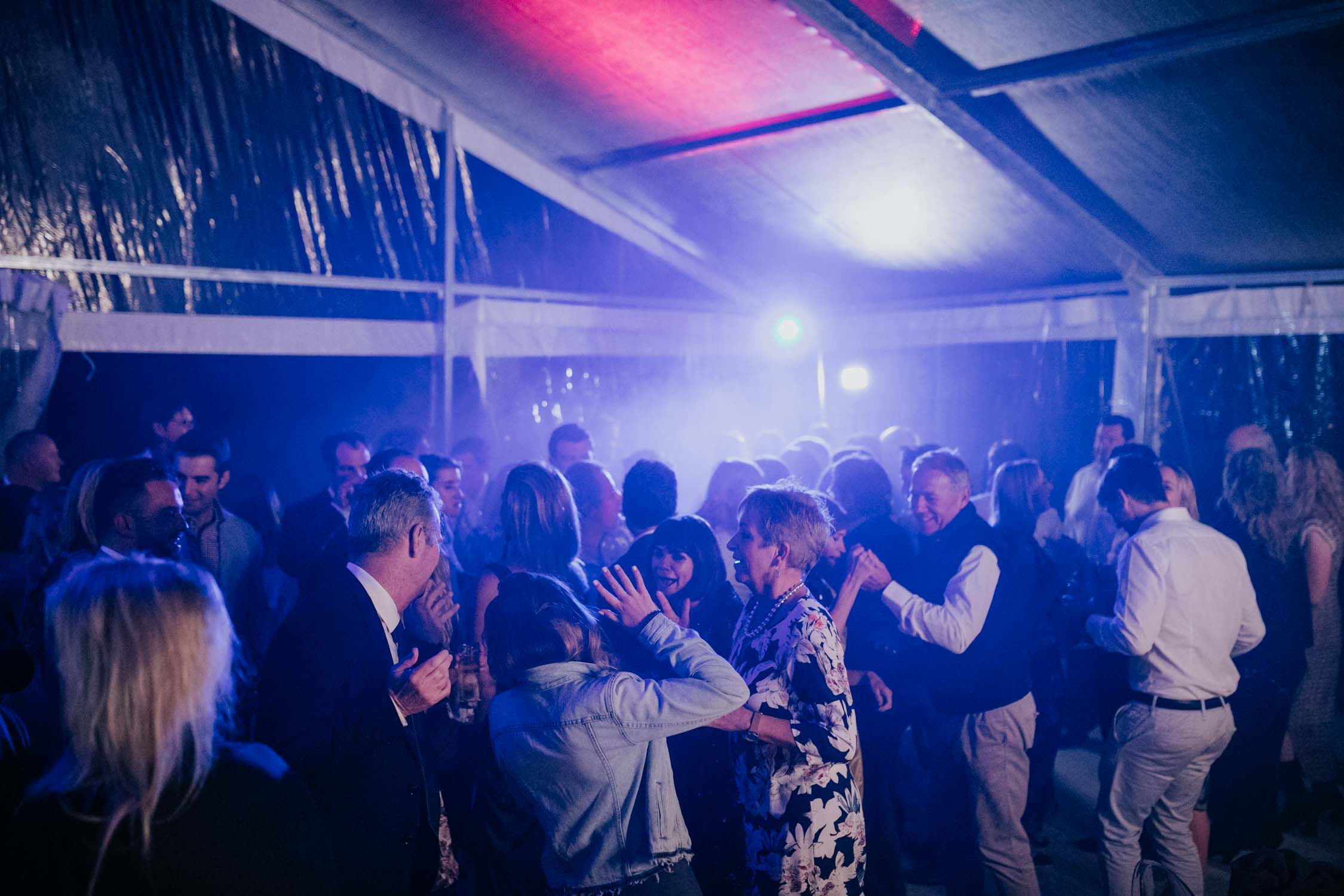 Fun photographs of guest dancing and having the best time at a wedding reception with blue and pink lights