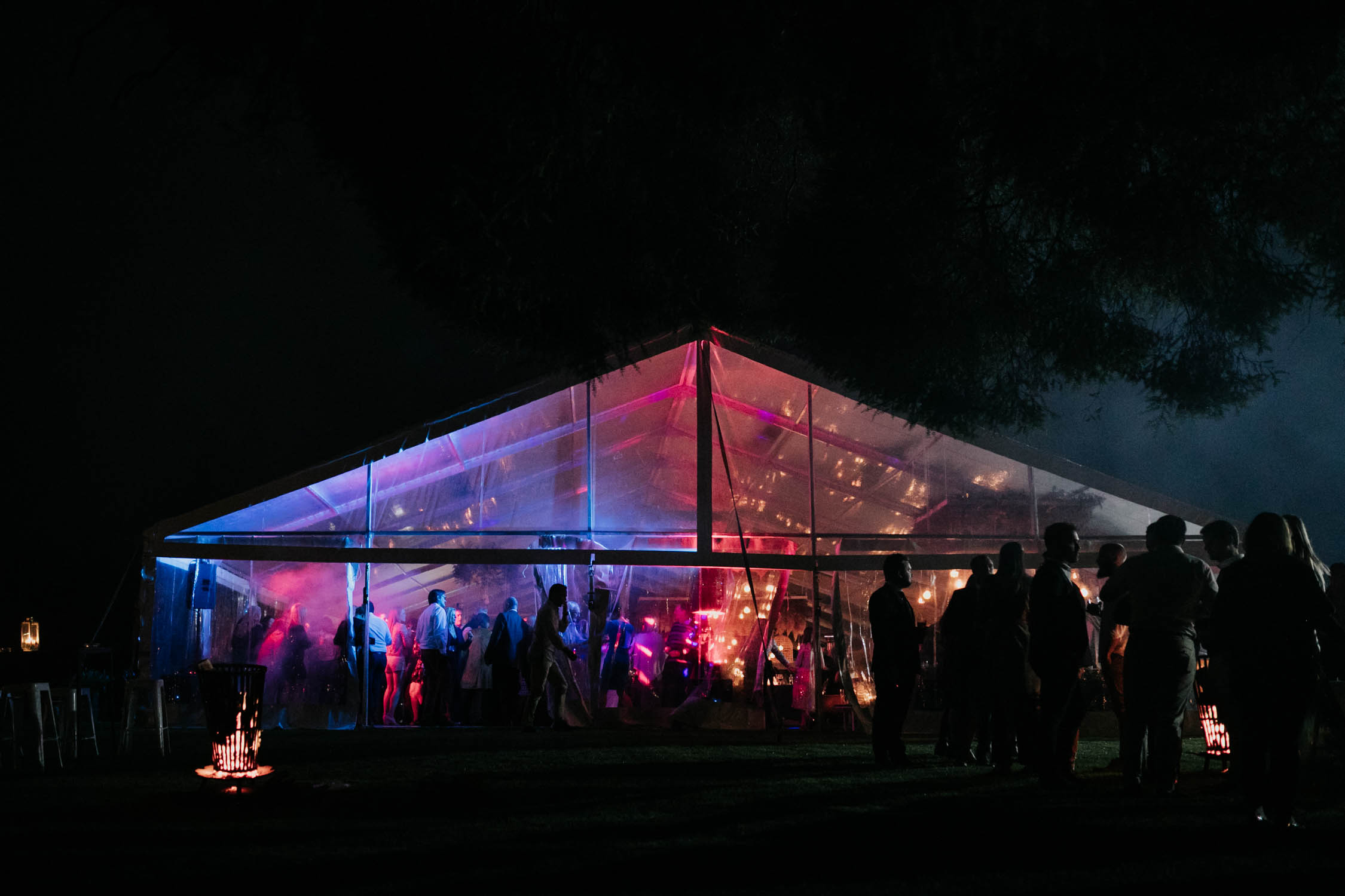 Fun photographs of guest dancing and having the best time at a wedding reception with blue and pink lights seen from outside the glass tent