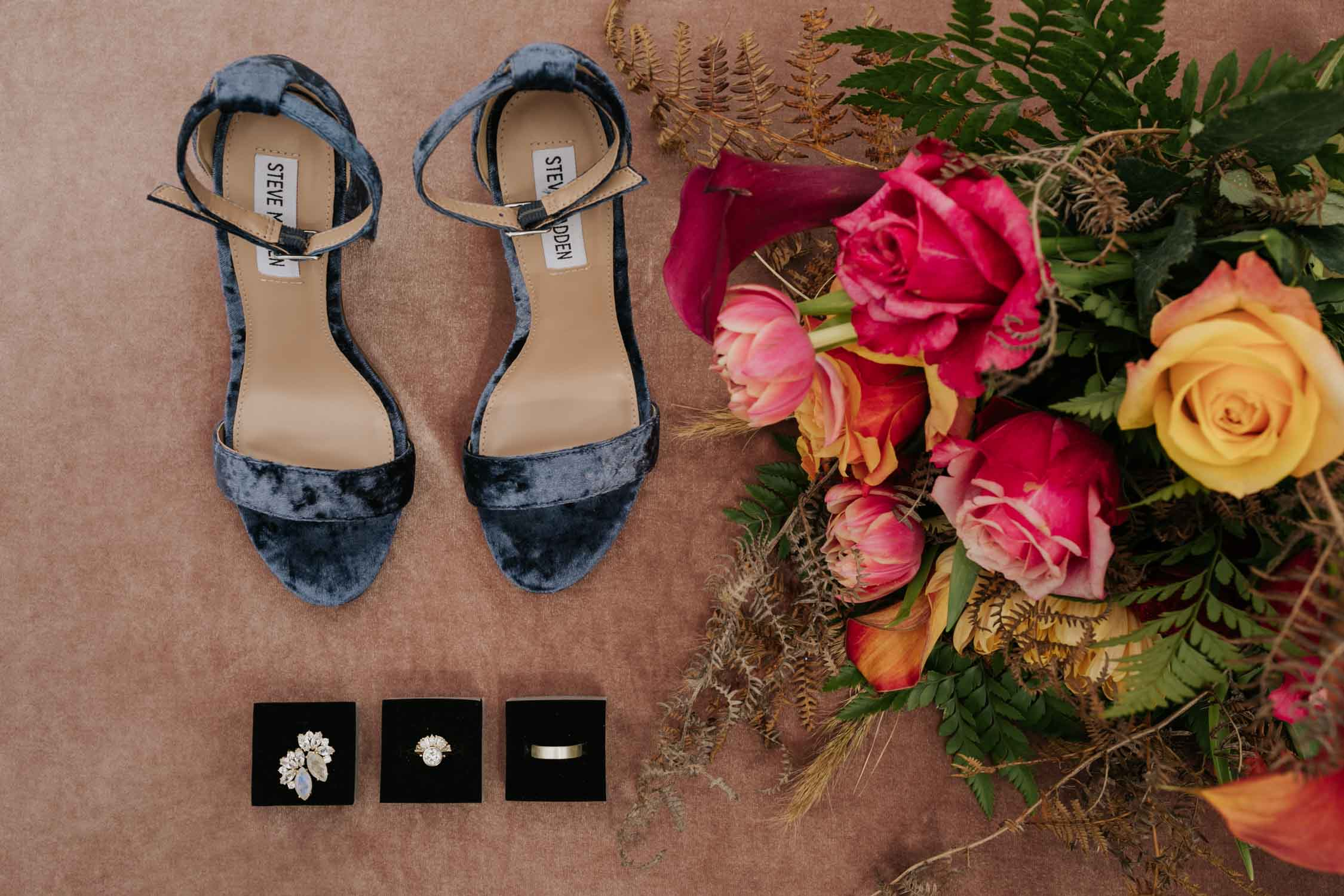 Wedding flat lay with blue velvet shoes, wedding accessories and pink and orange rose bouquet