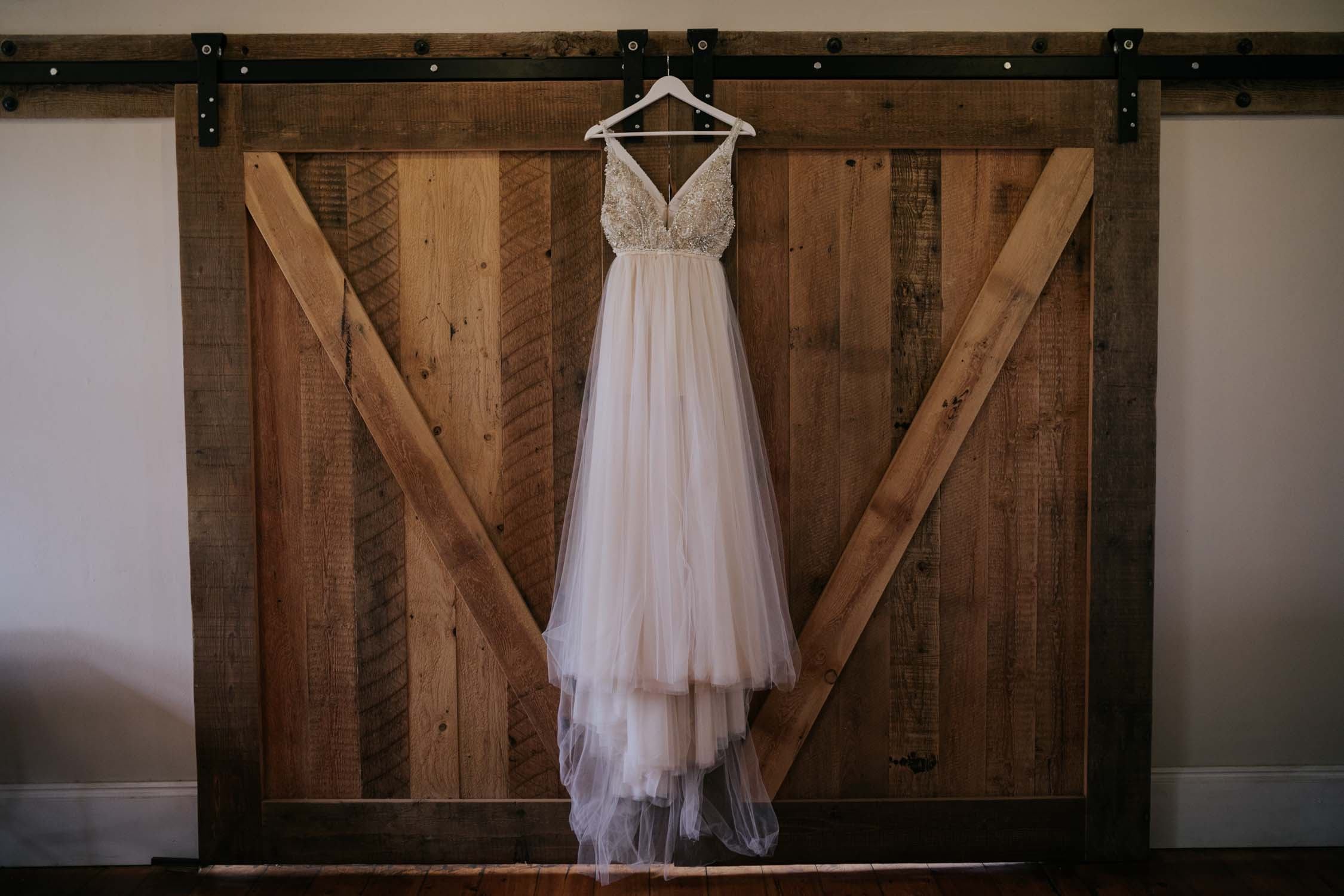 Wedding dress with beads and lace hanging on wooden farm doot