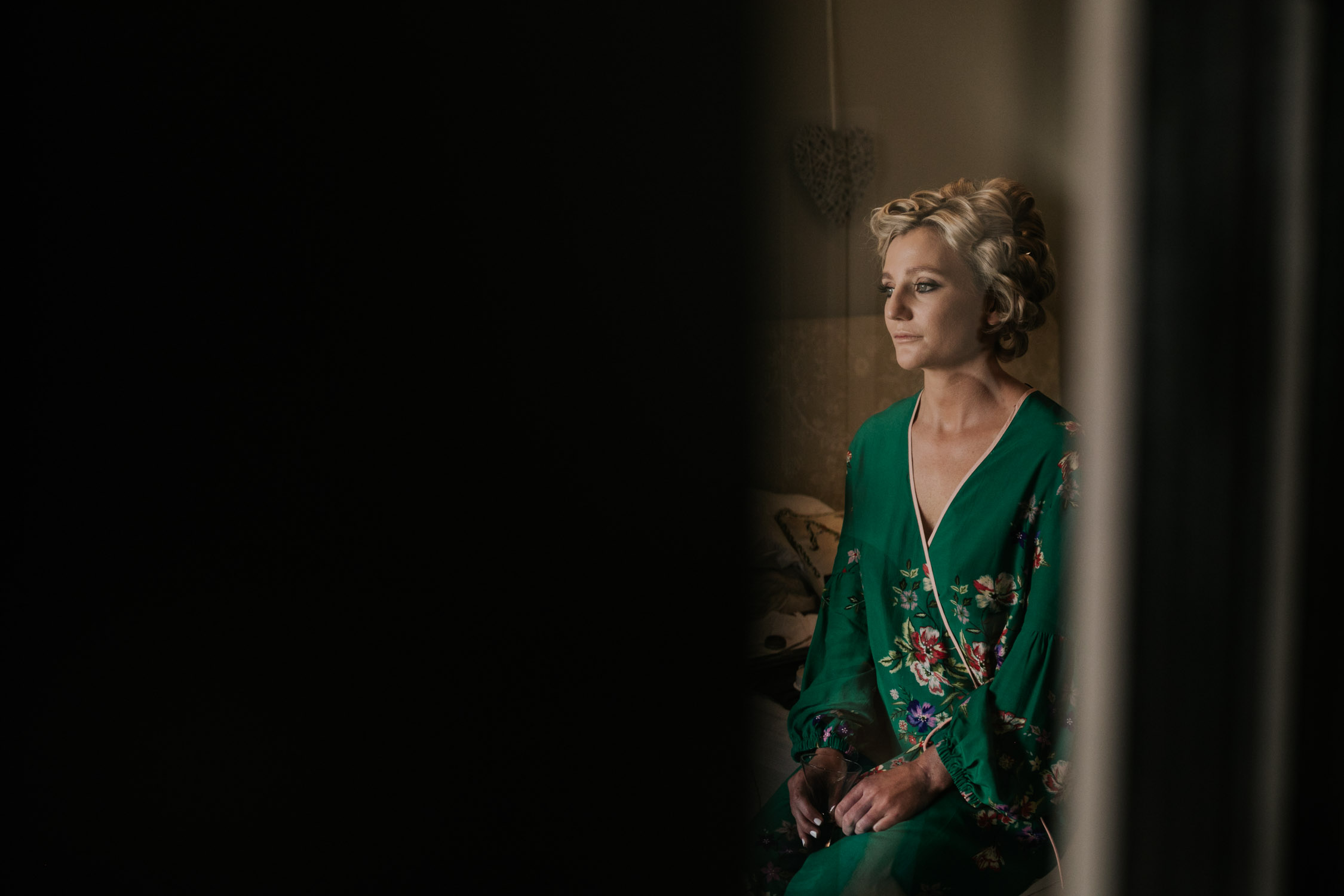 blonde bride sitting in a farm house with curlers in her hairs wearing a green Chinese dressing gown