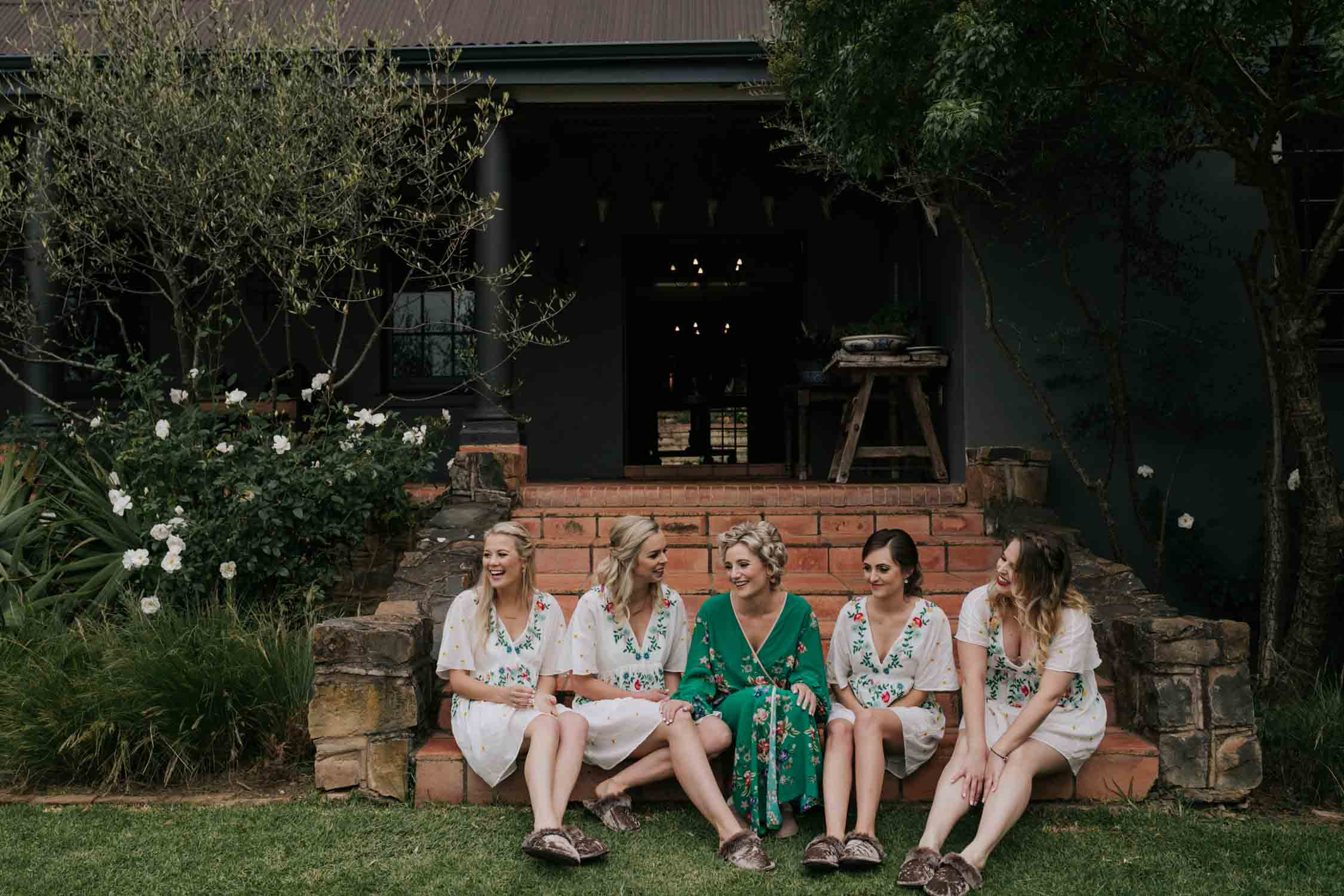 bride wearing a green Chinese dressing down and curlers in her hair sitting with her bridesmaids on the steps of her farm house