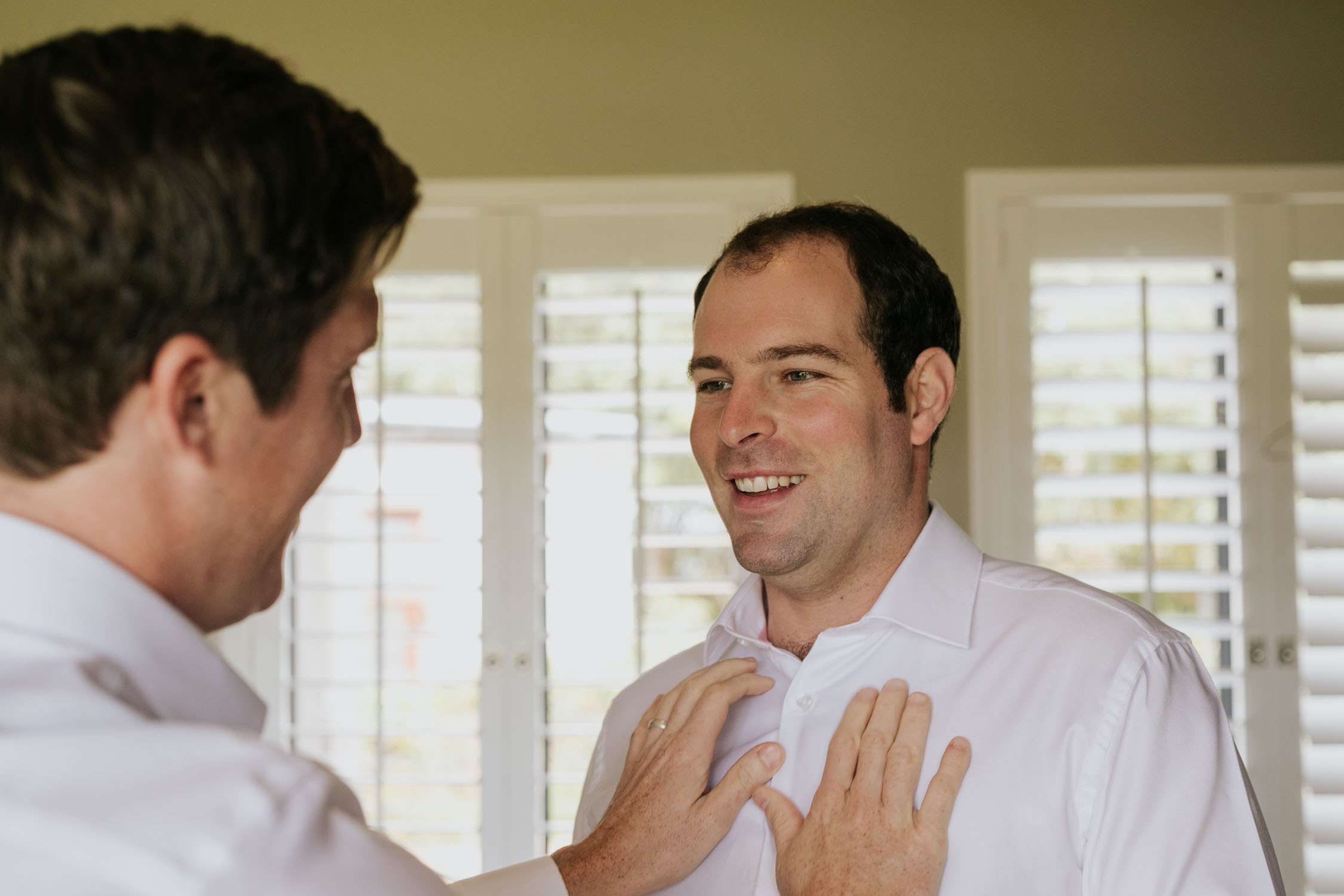 Groom wearing a white shirt smiling and having a real moment with his friend while getting dressed on his wedding day
