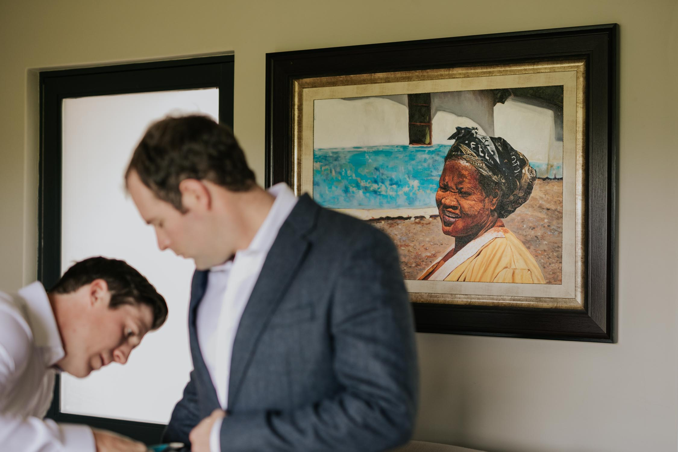 Groomsman helping groom get ready for his wedding day. Groom is wearing a white shirt and grey jacket and is standing in front of a painting of an African woman.