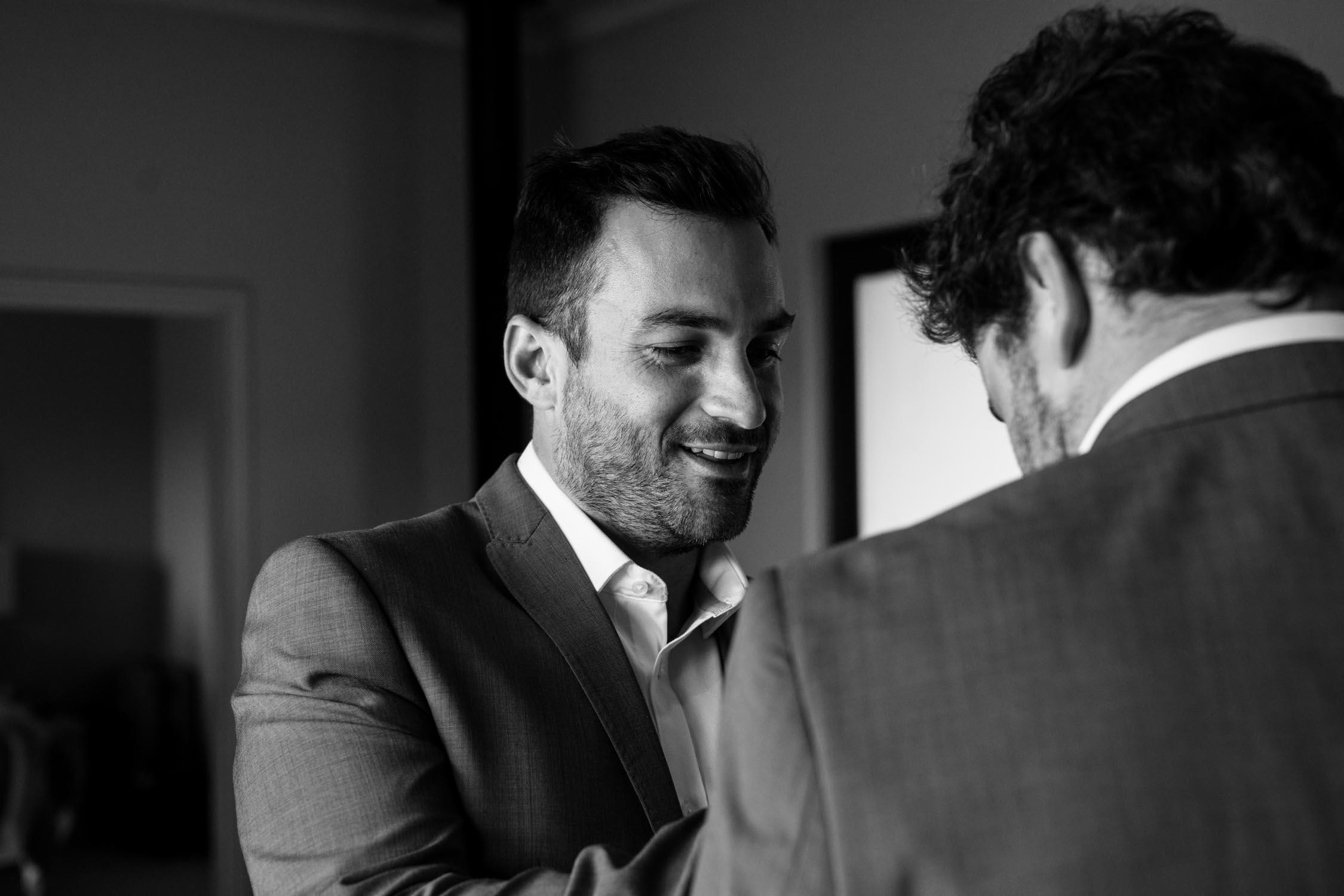 Groomsman with beard helping the groom get ready on his wedding day.