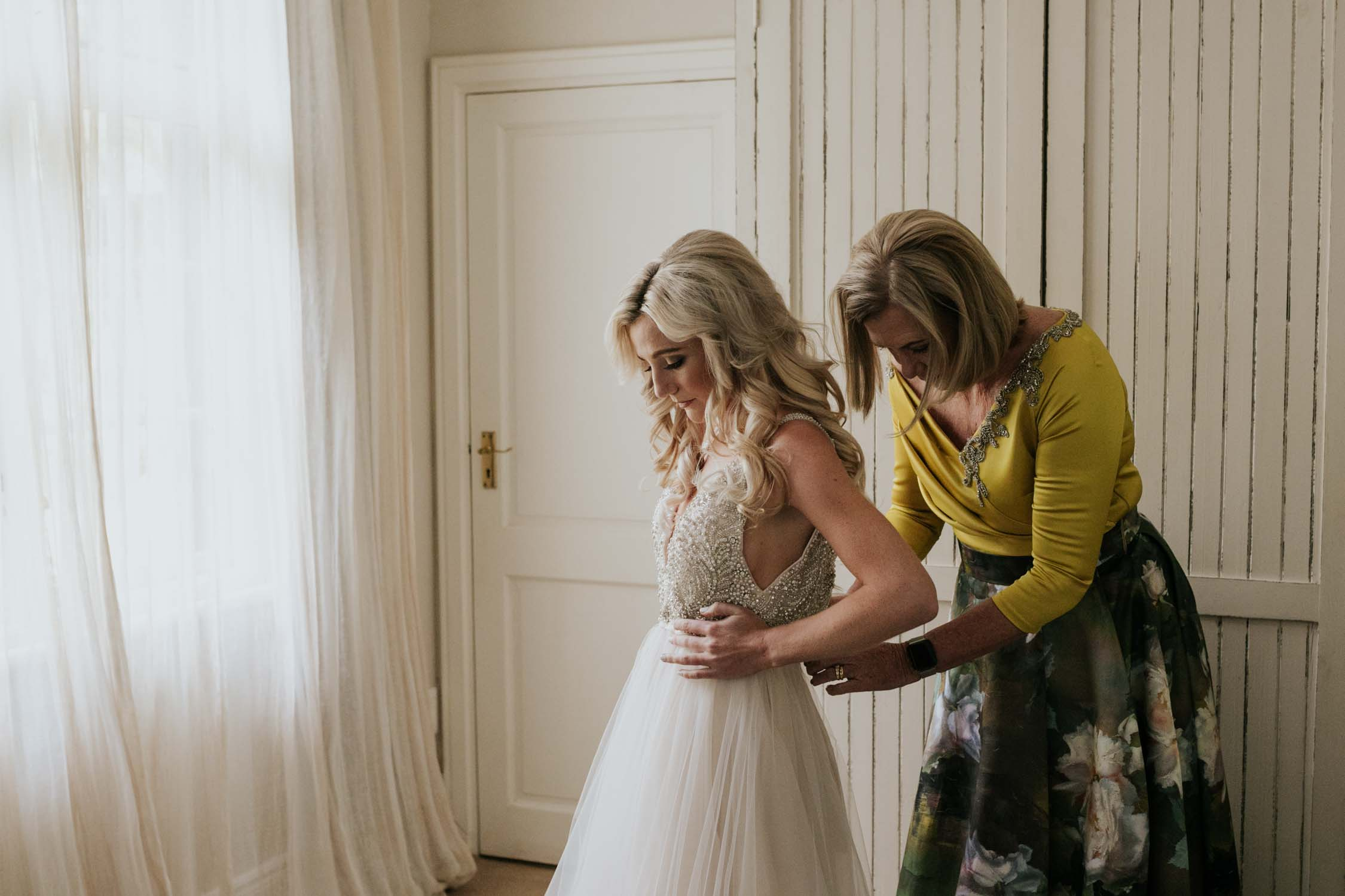 Mother of the bride helping her daughter get into her wedding dress. They are standing in front of a window and bride is wearing a see through dress with shorts underneath the skirt.