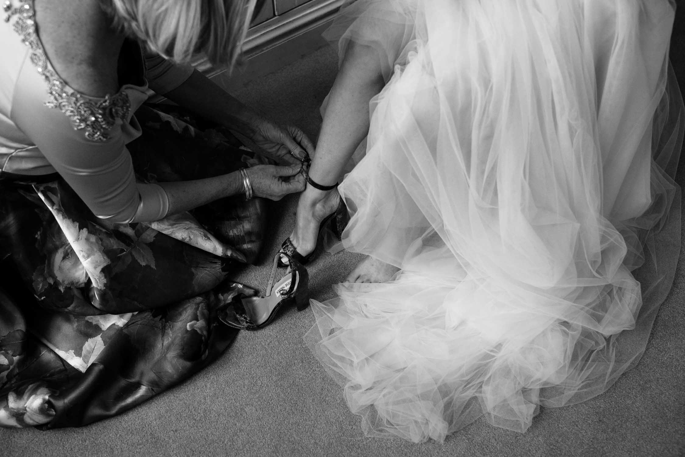 Mother of the bride helping her daughter put on her wedding shoes.