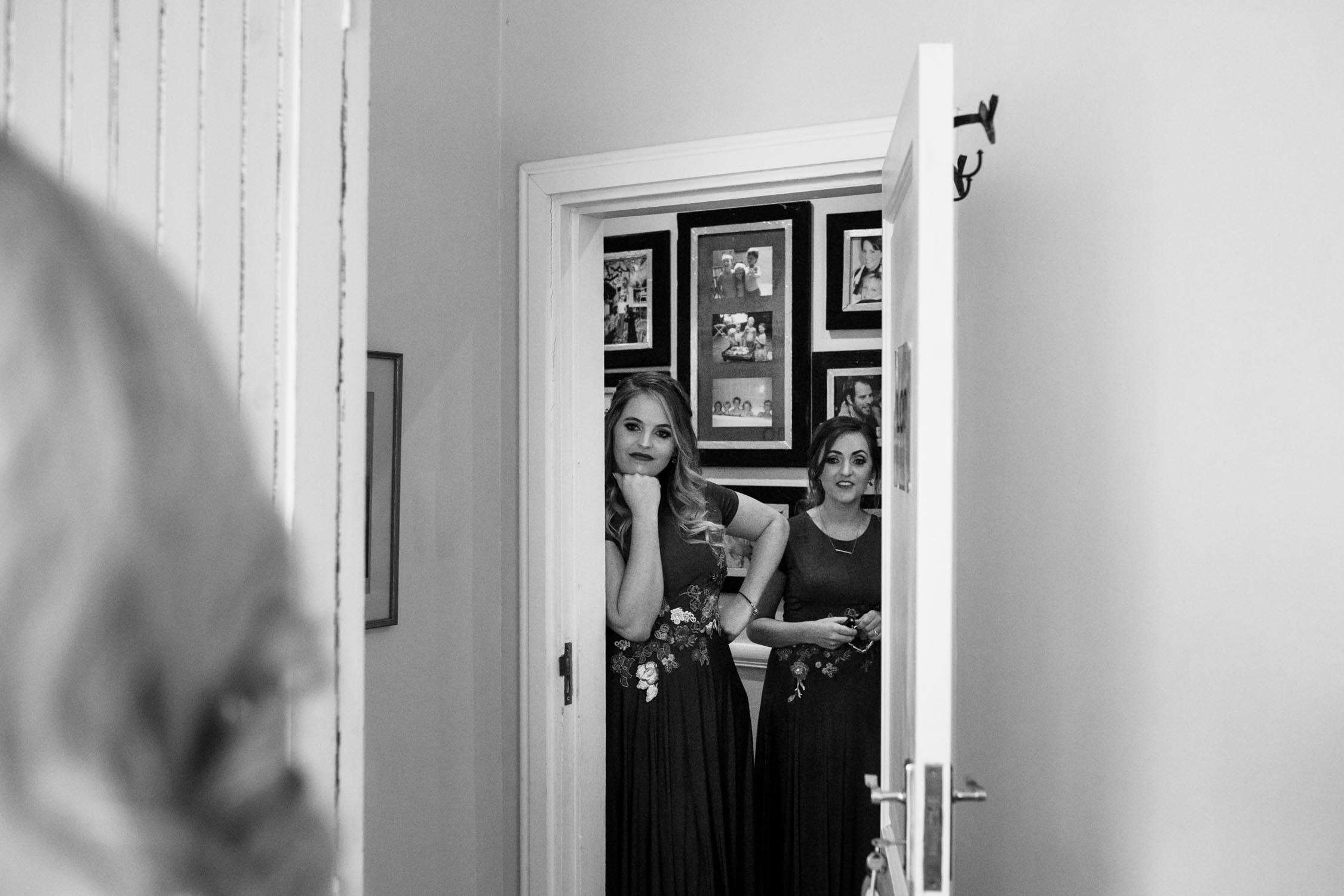 Bridesmaids standing at the door watching the bride get ready.