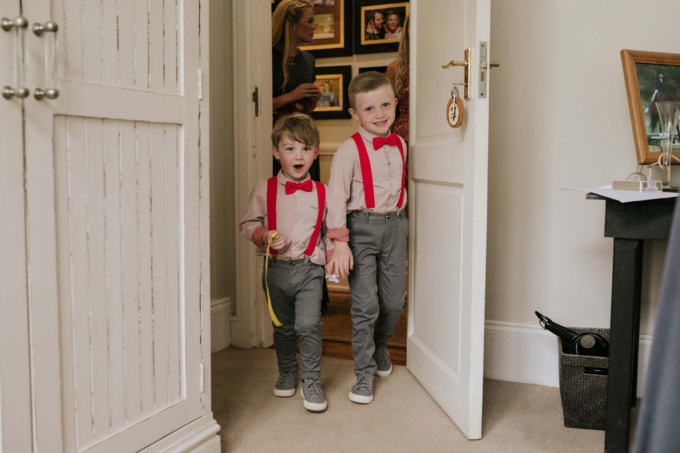 Cute page boys coming in the door to see the bride for the first time wearing red bowties and suspenders, grey pants and checked shirts.