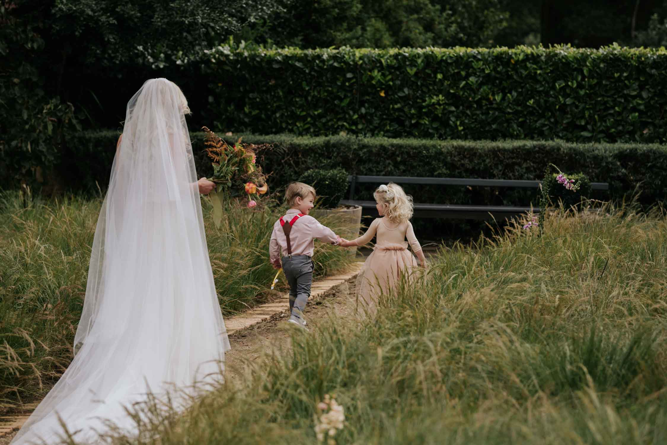 Flower girl wearing pale pink dress and page boy wearing grey and red walk in front of bride down a garden path. Bride is wearing a veil.