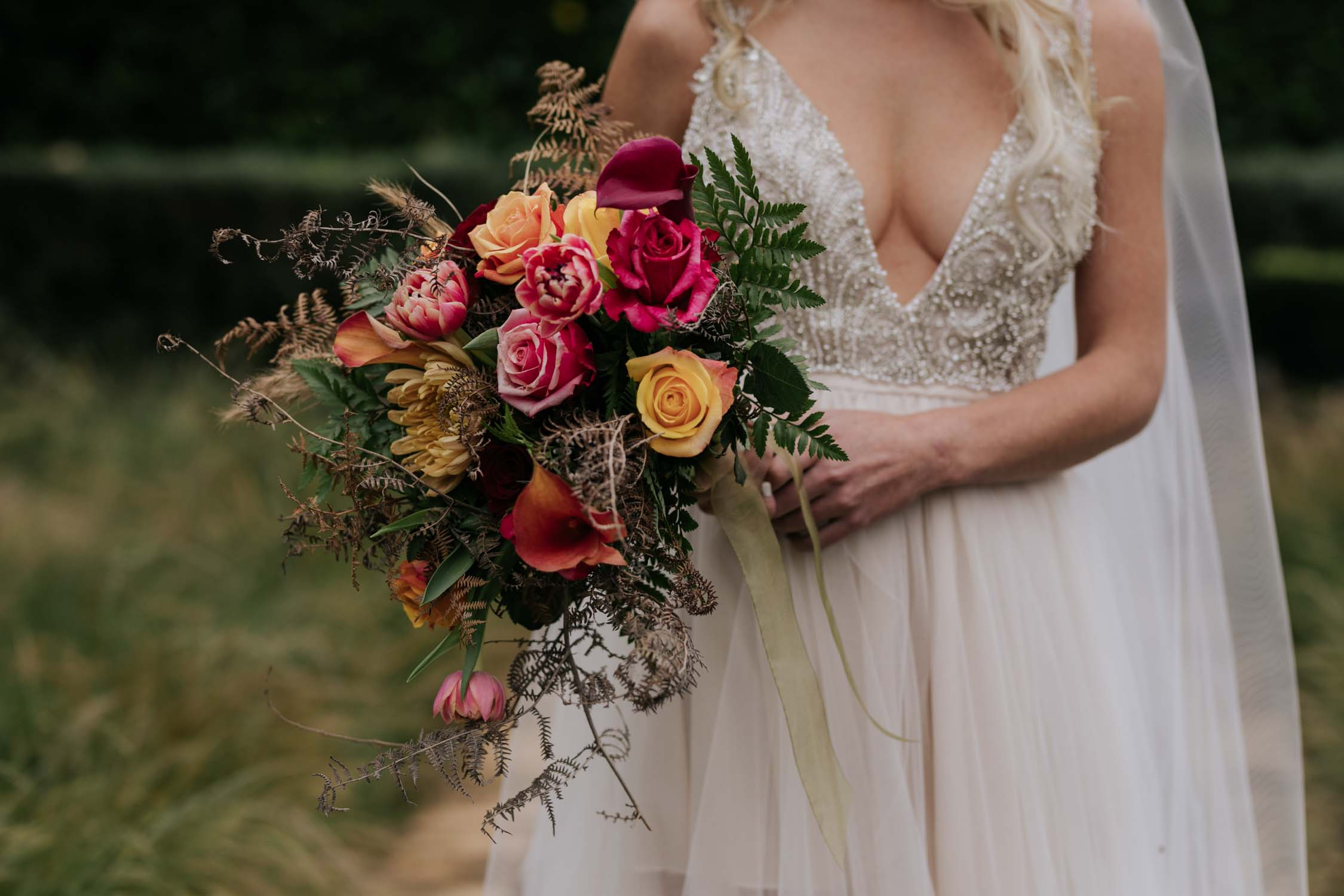 Bride wearing a low cut dress with beautiful and detailed beadwork with a skirt that is see through and cute shorts underneath almost like a jump suit underneath a wedding dress. She is holding a wedding bouquet of burnt orange pink and red flowers and roses with dried ferns and grass in it.