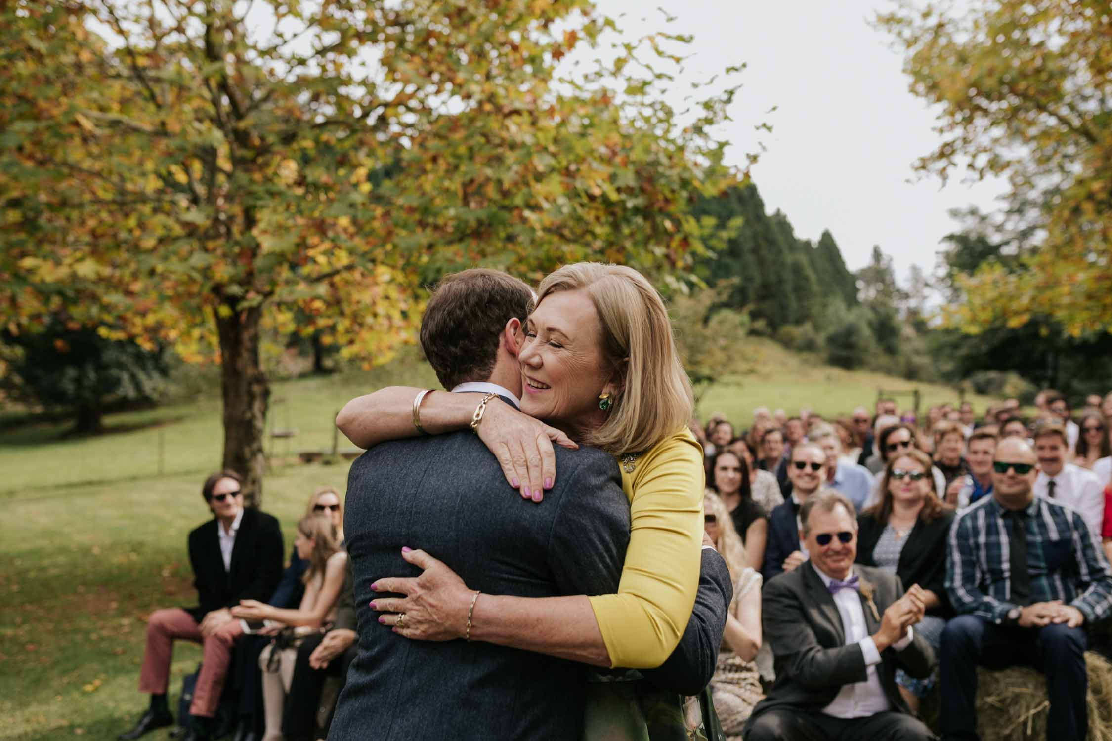 Bride's mother wearing yellow top hugging groom warmly before bride walks down the aisle. Real and emotional moment.