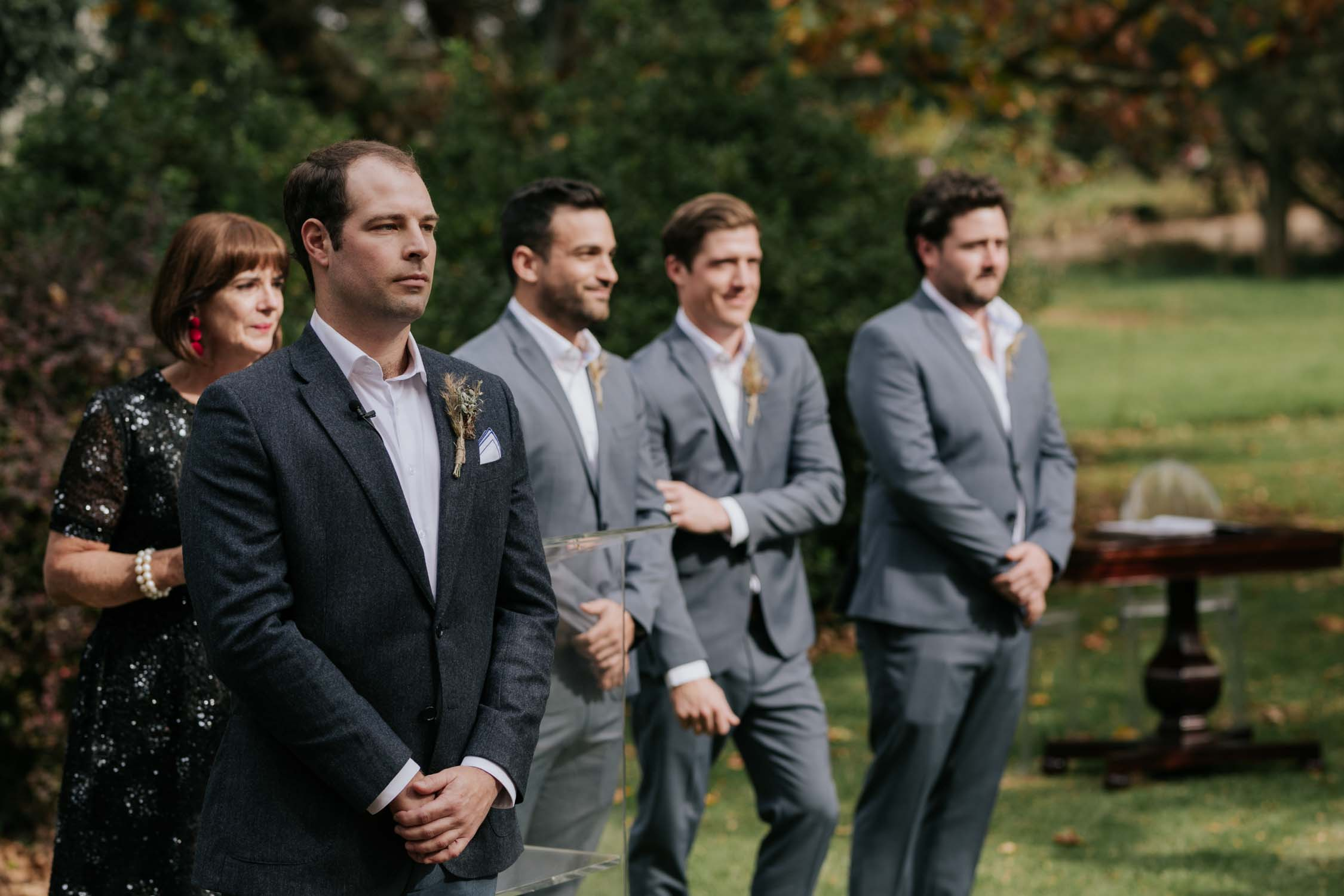 Emotional groom watching his bride walk down the aisle. He is standing with his groomsmen wearing grey suits.