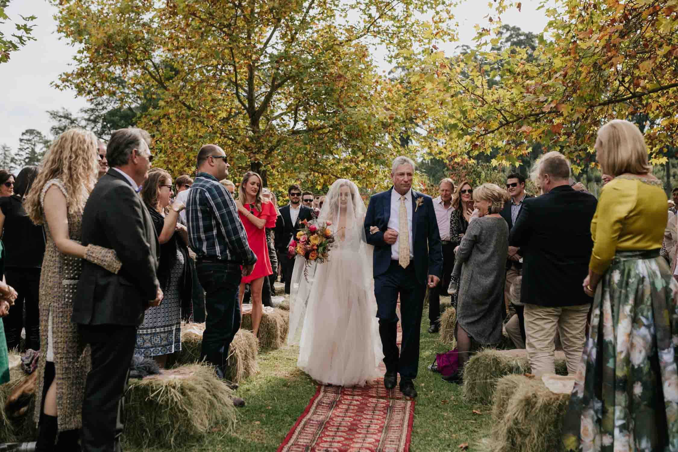 Bride wearing a low cut dress with beautiful and detailed beadwork with a skirt that is see through and cute shorts underneath almost like a jump suit underneath a wedding dress. She is holding a wedding bouquet of burnt orange pink and red flowers and roses with dried ferns and grass in it. Her dad is walking her down the aisle on a red Persian carpet under the Autumn trees in a garden and they are very emotional.